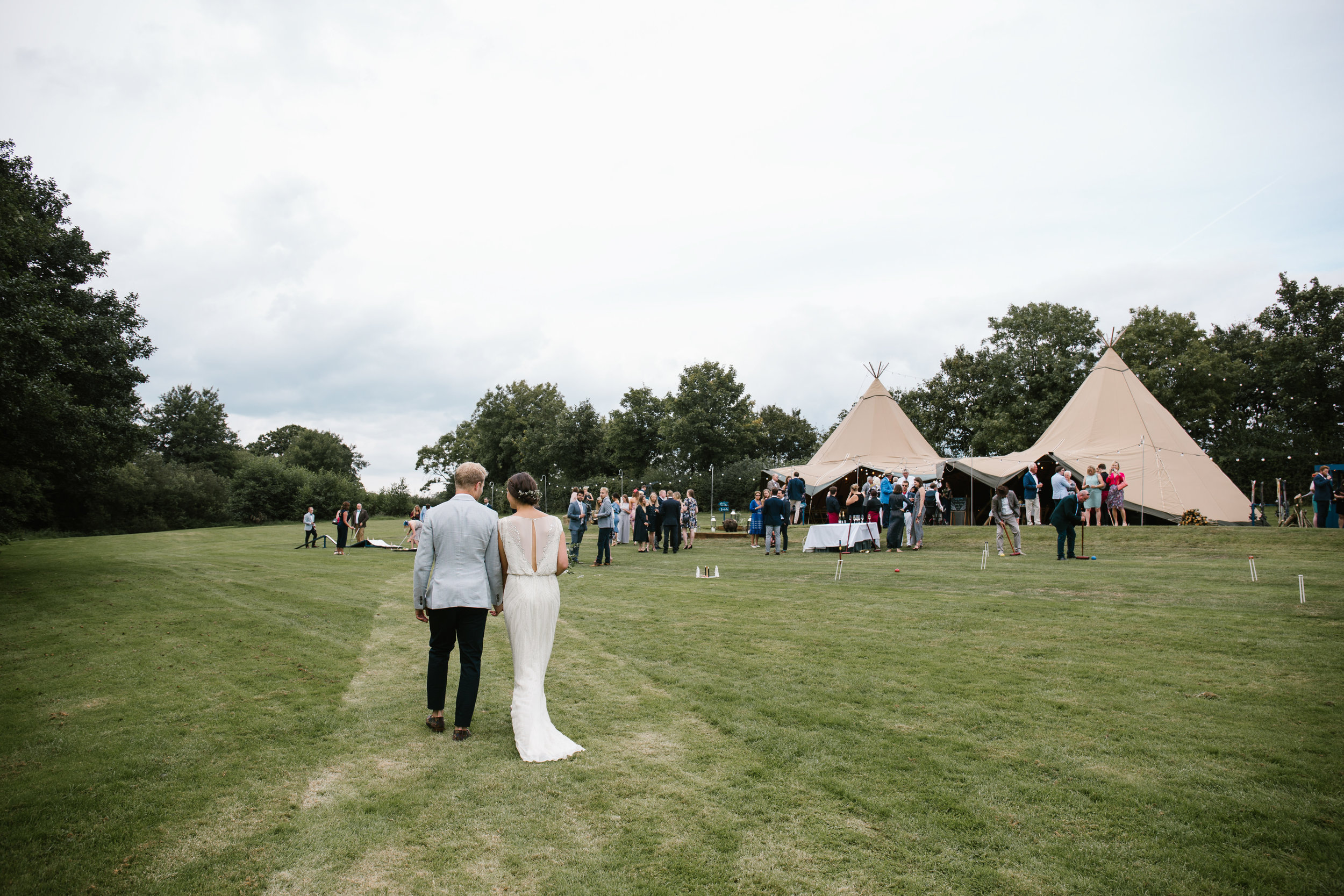 documentary shot of bride and groom walking back to their tipi with all their wedding guests after their outdoor wedding ceremony