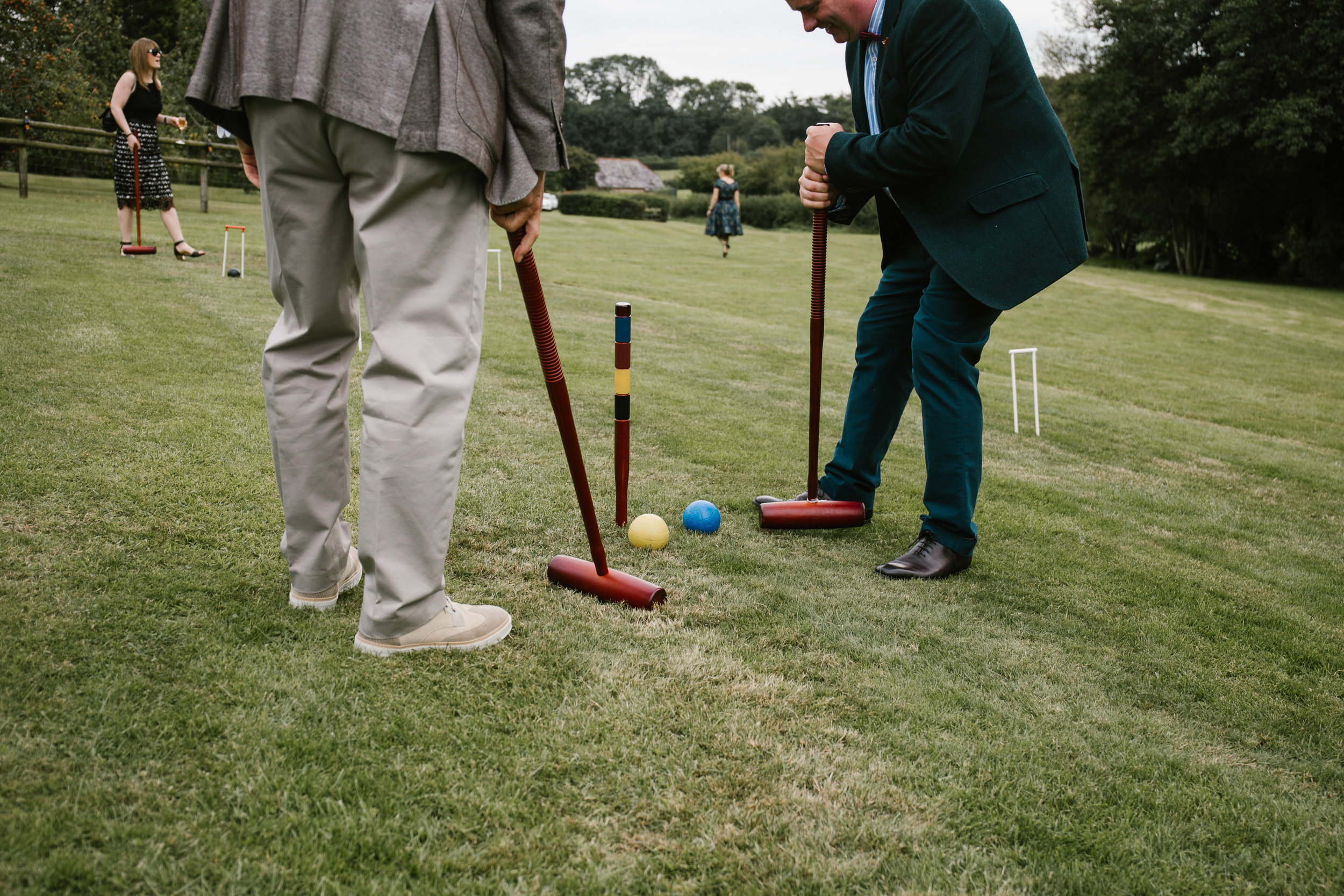 men playing lawn games at outdoor wedding