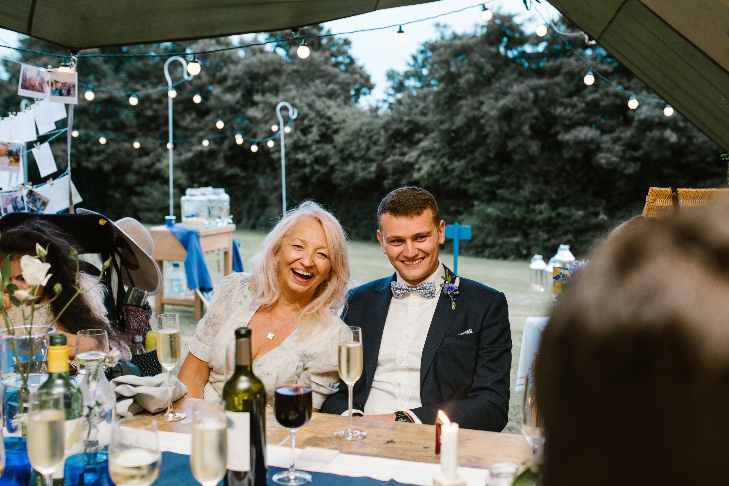wedding guests laughing together as they laugh at speeches