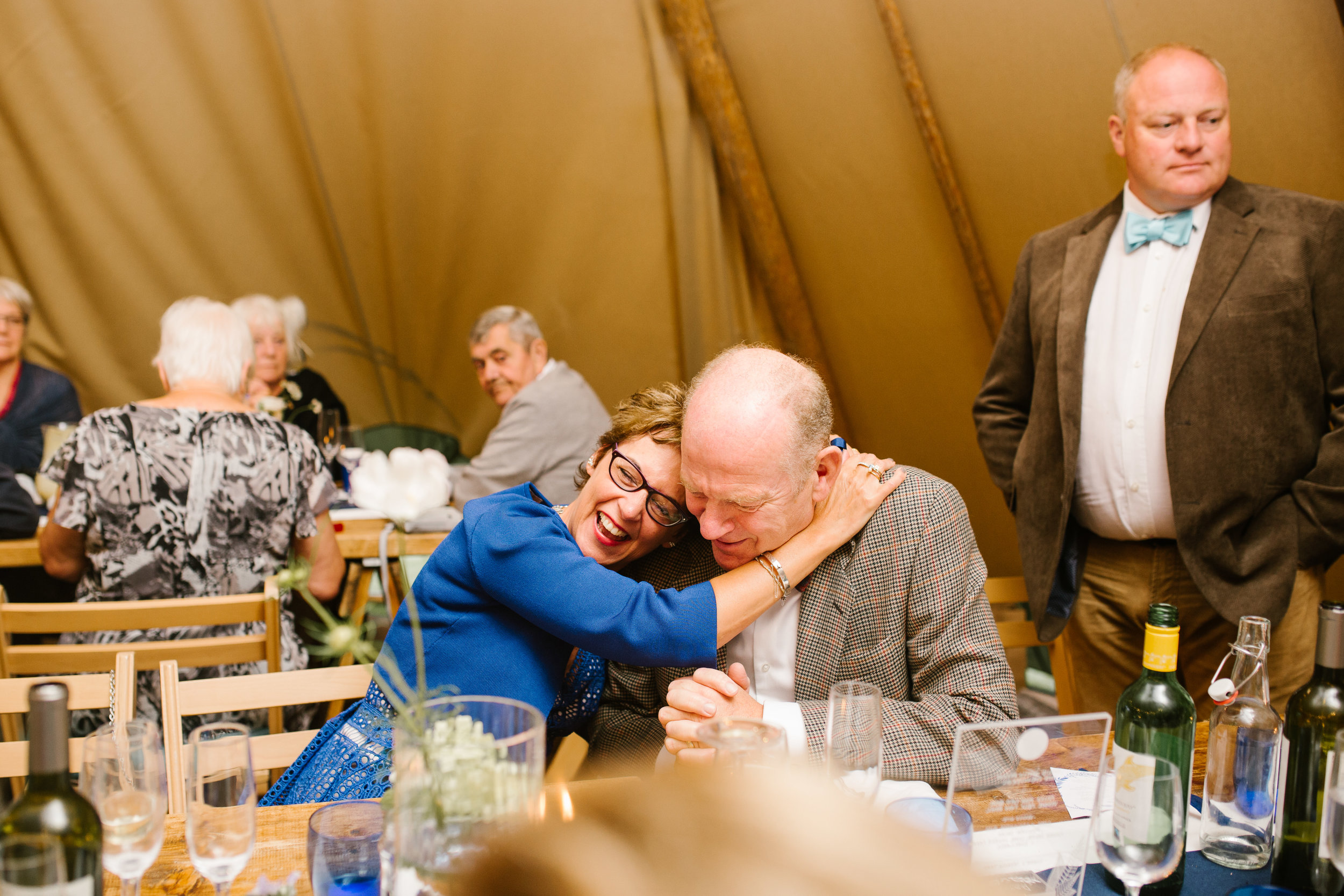 natural photo of wedding guests hugging one another during the wedding speeches