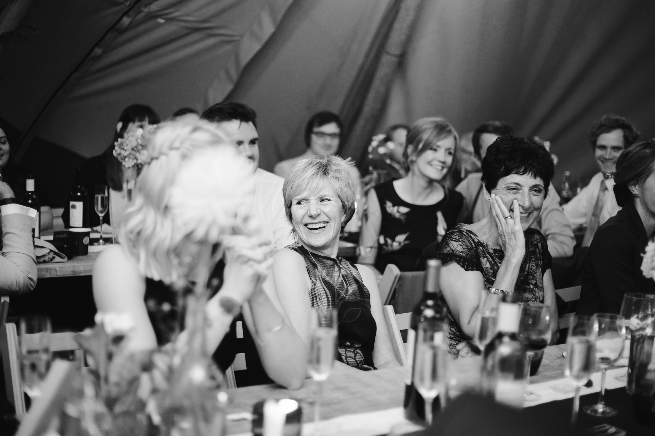 black and white photo of mother of the groom laughing naturally during the wedding speeches