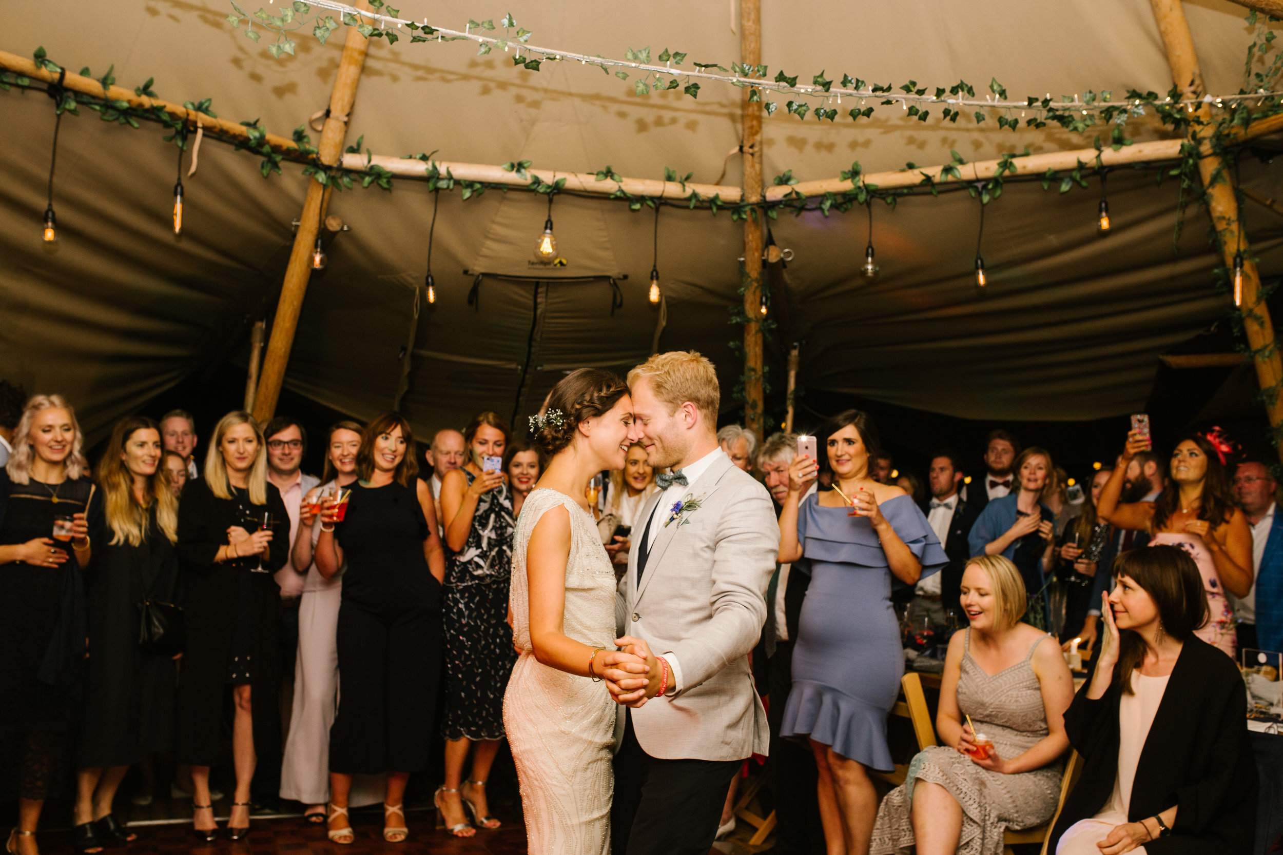 bride and groom dancing together on the dance floor for their first dance in their tipi