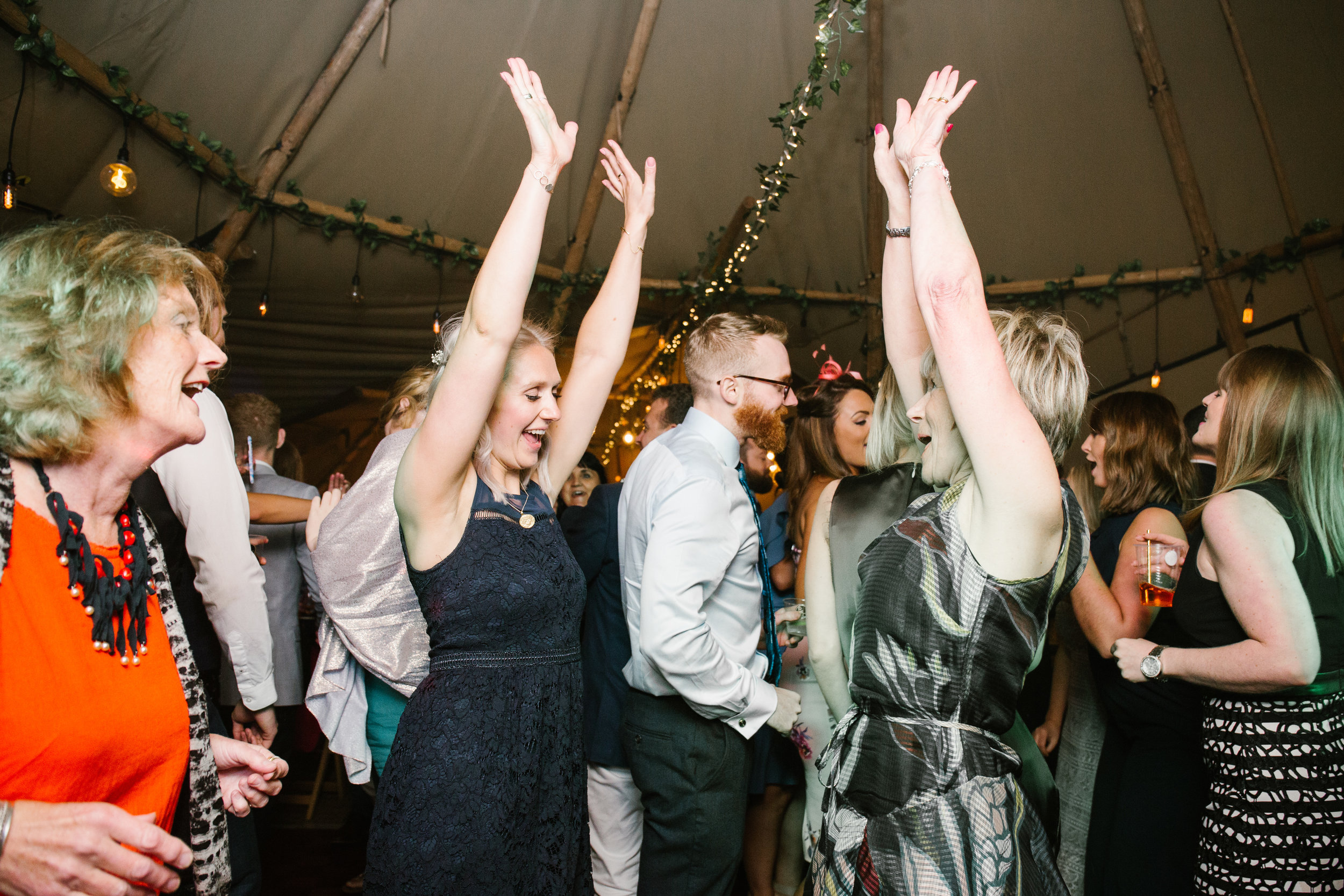mother and daughter dancing on the dance floor of a wedding with their arms high in the air