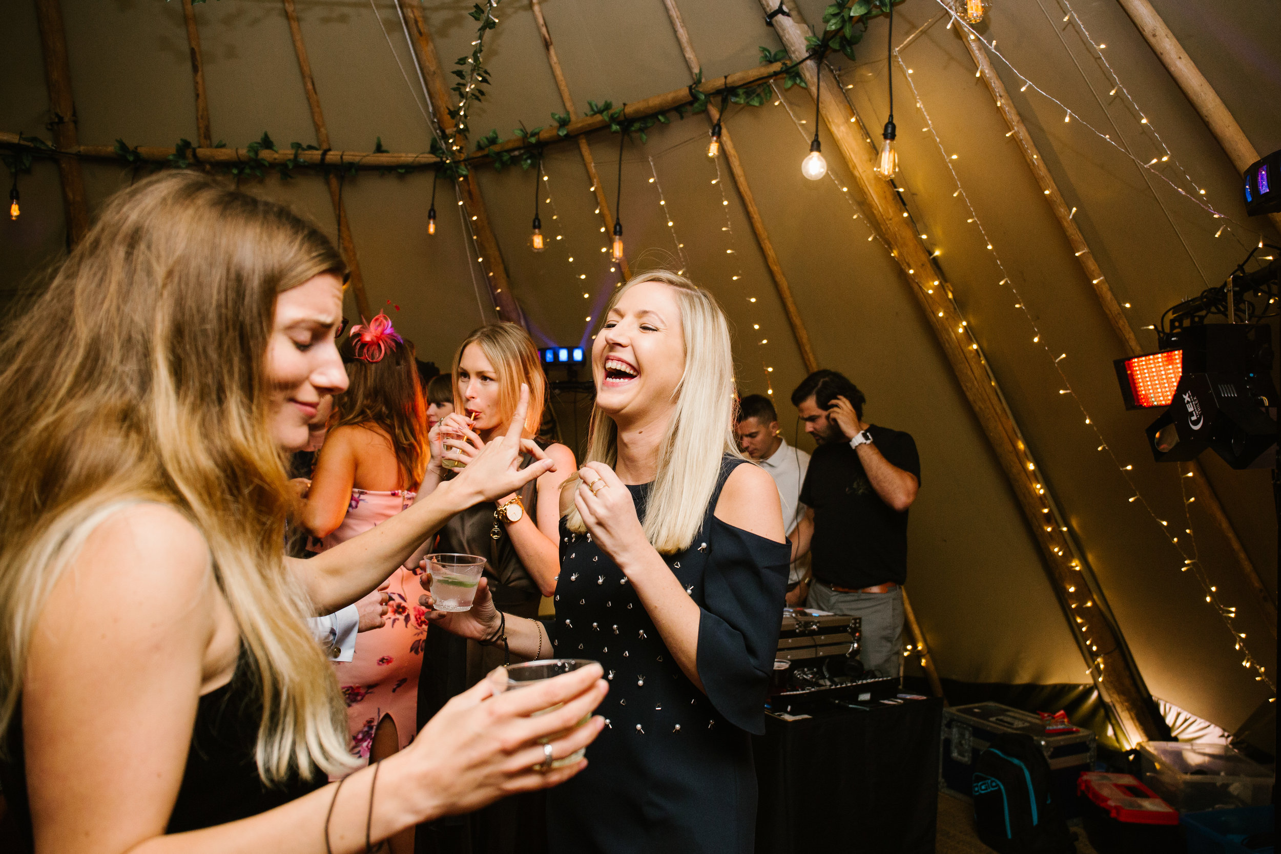 natural photo of wedding guests laughing on the dance floor at a tipi wedding