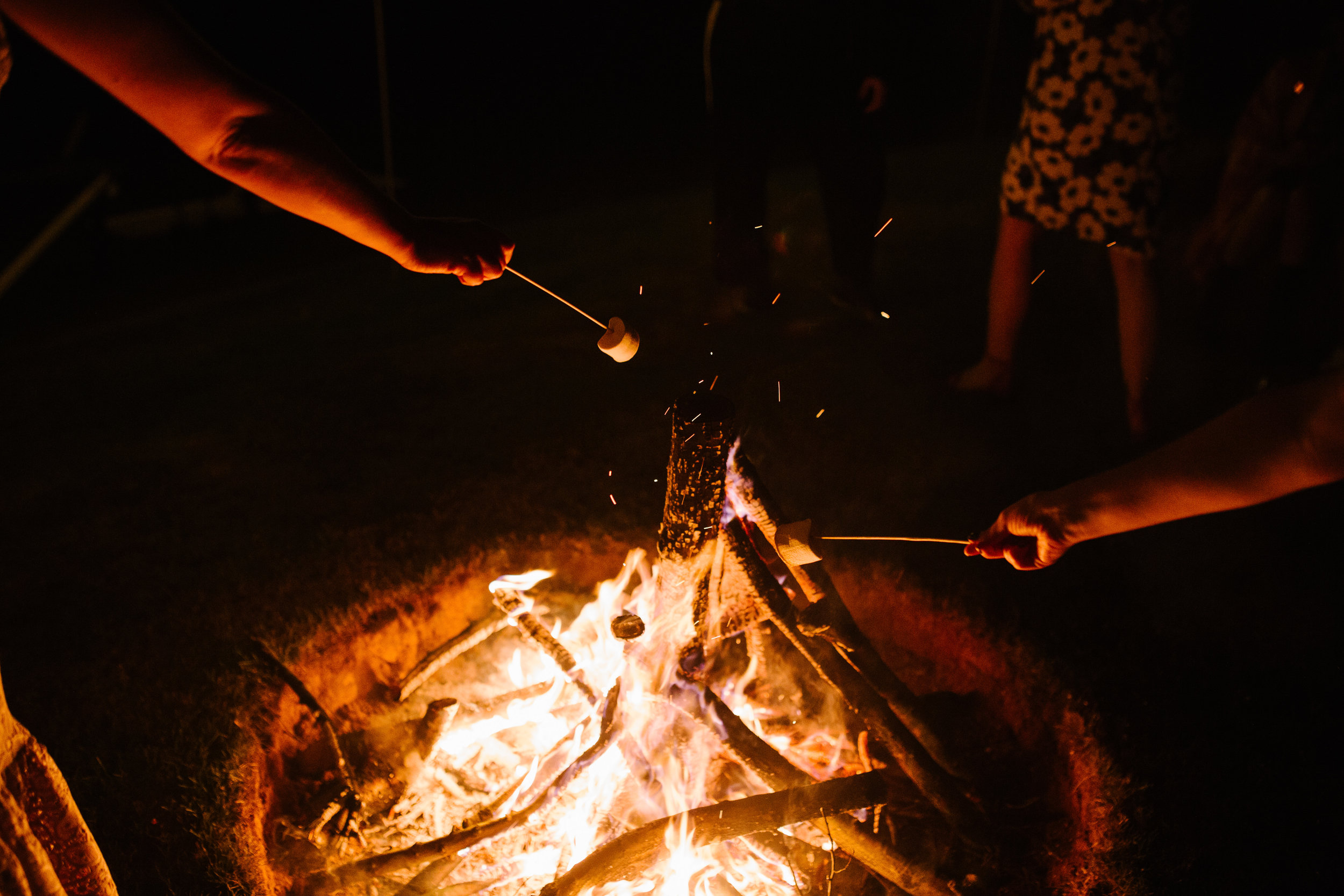 fire pit outside a tipi wedding with guests roasting marshmallows