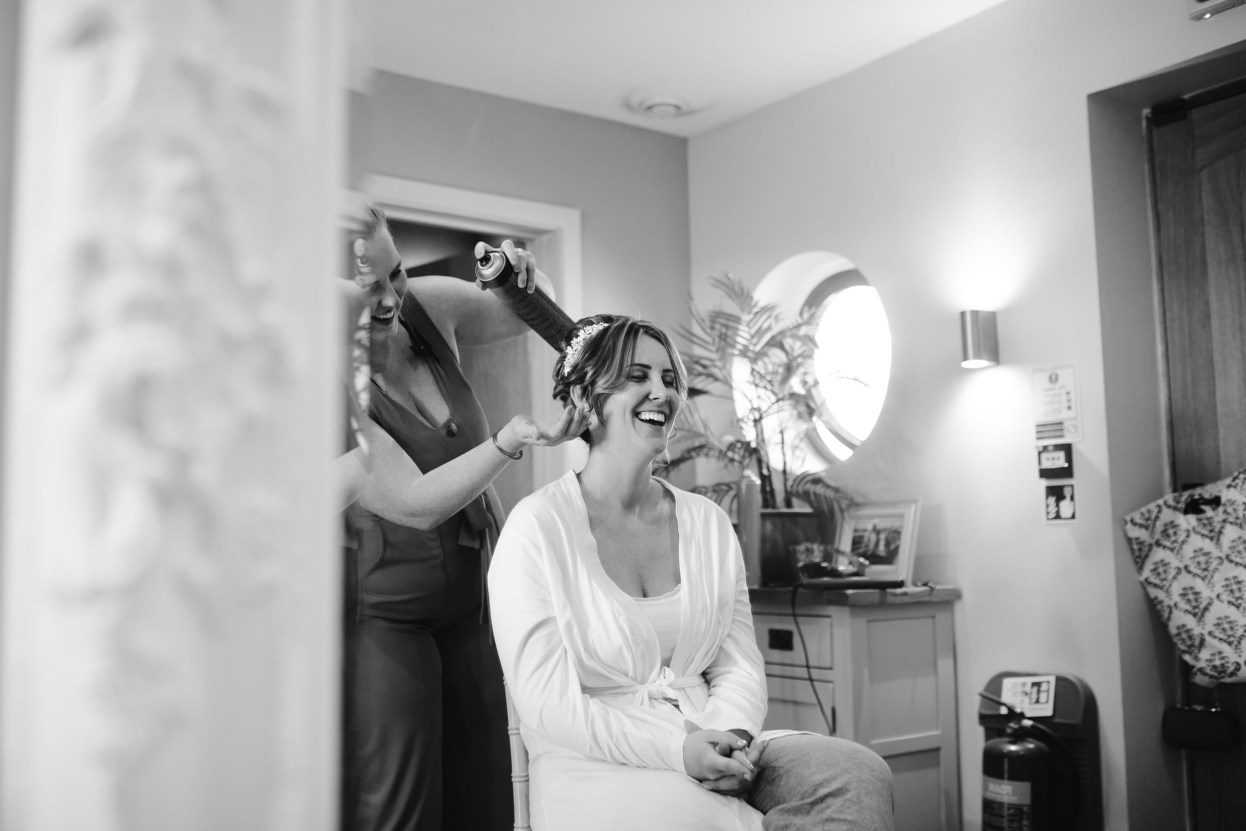 Black and white natural photograph of bride getting ready on the morning of her wedding