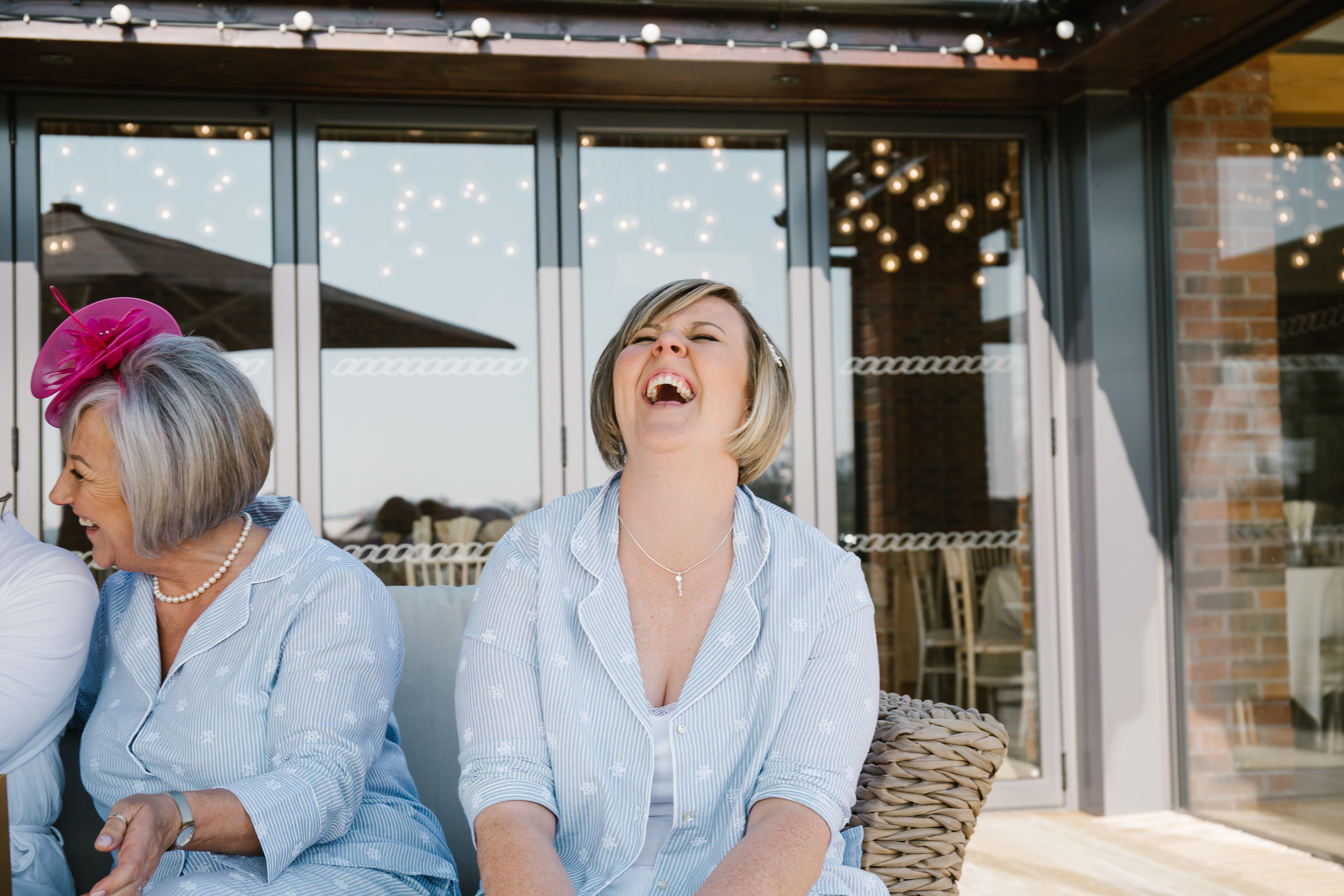 natural photo of bridesmaids laughing while the bride opens gift off groomm