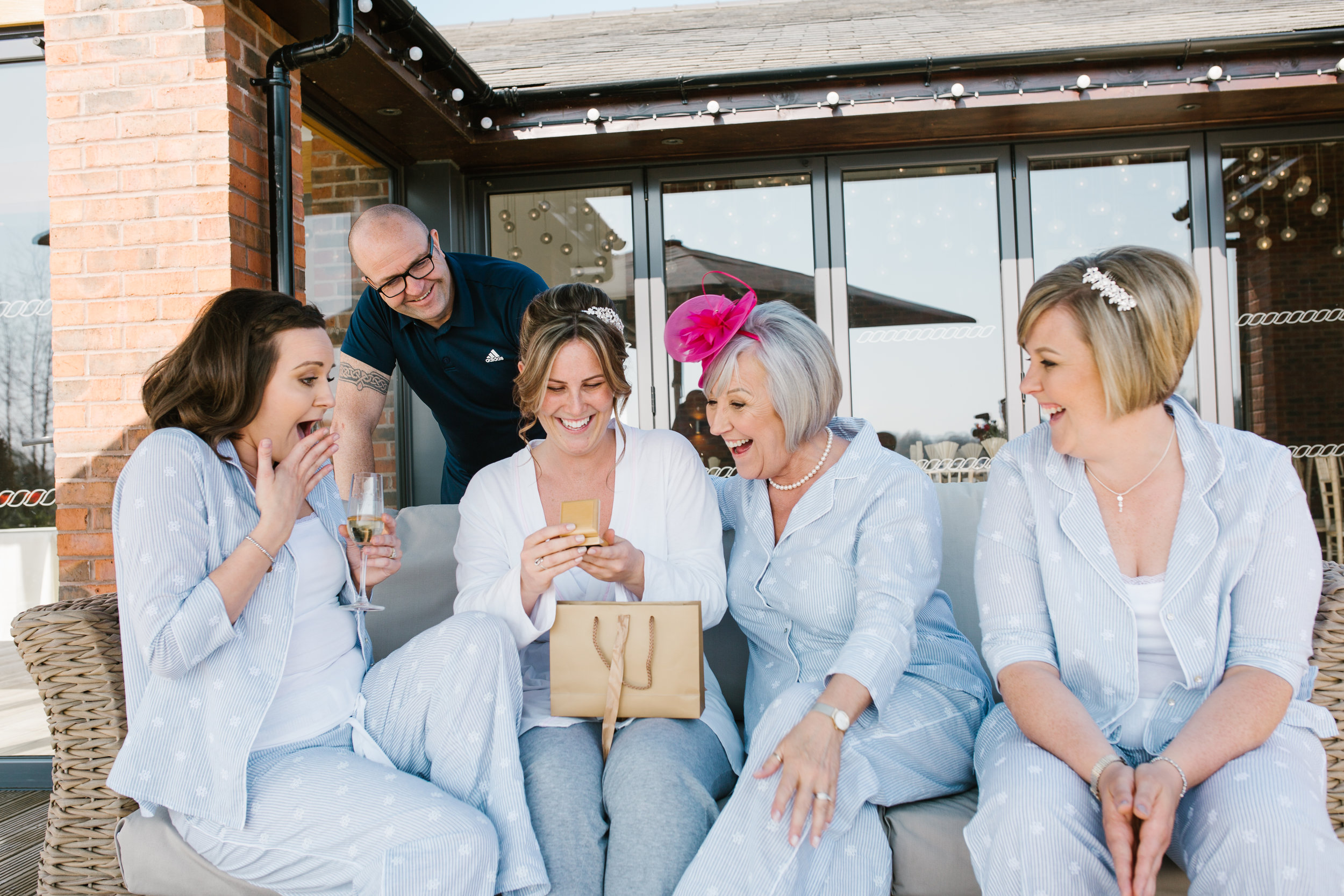 bride with her family opening presents off her groom on the morning off the wedding at the boat house aston marina