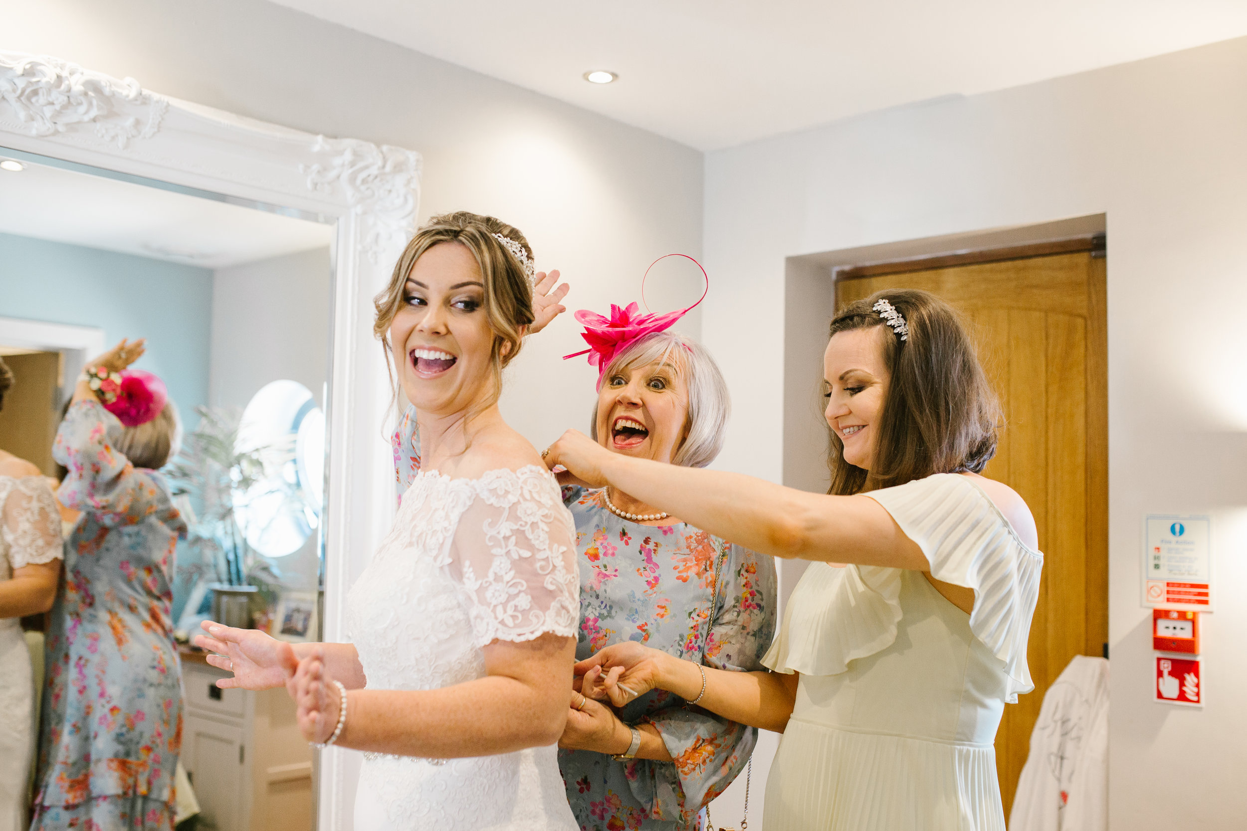 bridesmaids and mother of the bride fastening the brides wedding dress on the morning of her wedding