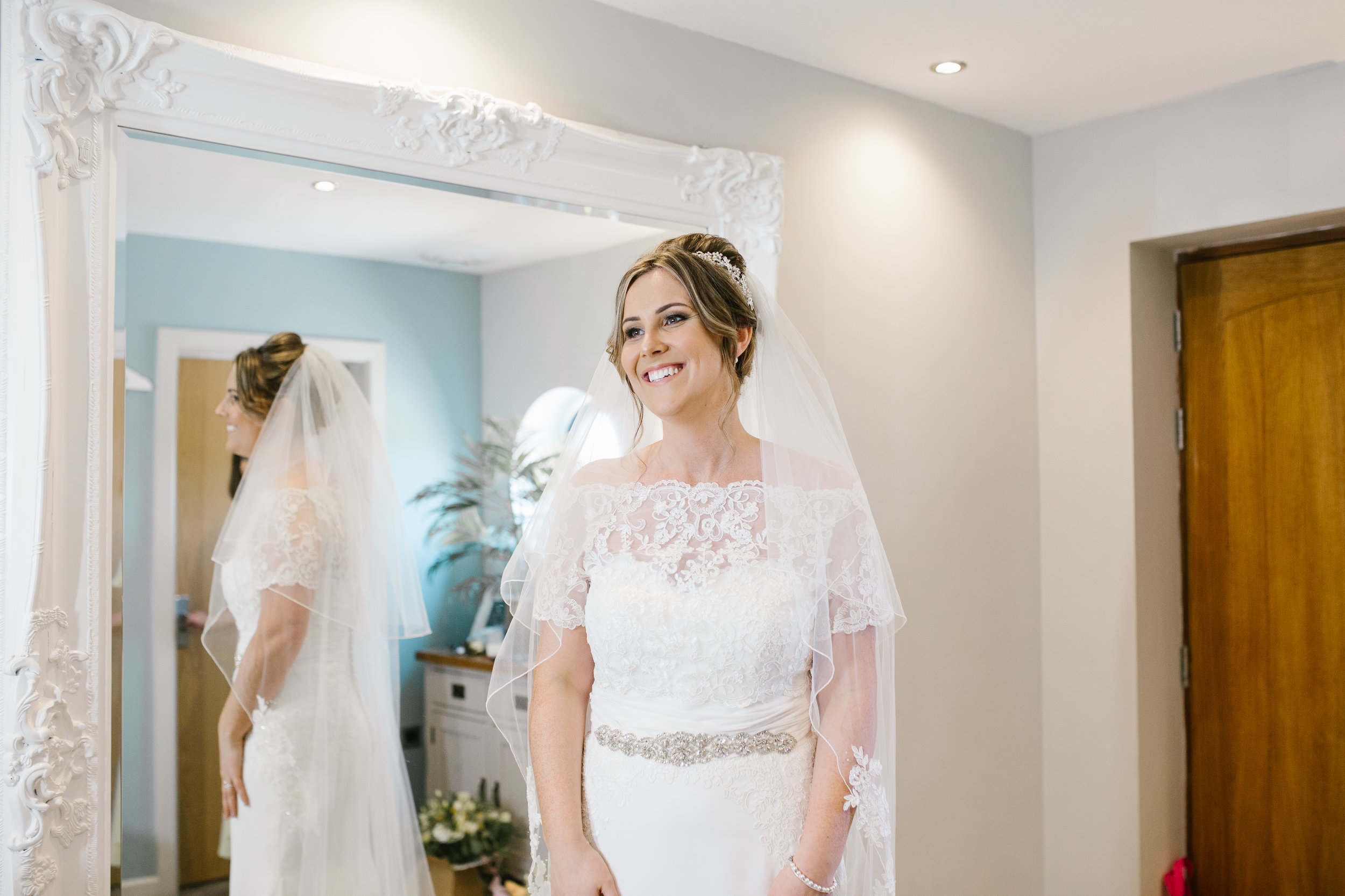 natural smiling photo of bride in her wedding dress just before she leaves to marry her groom