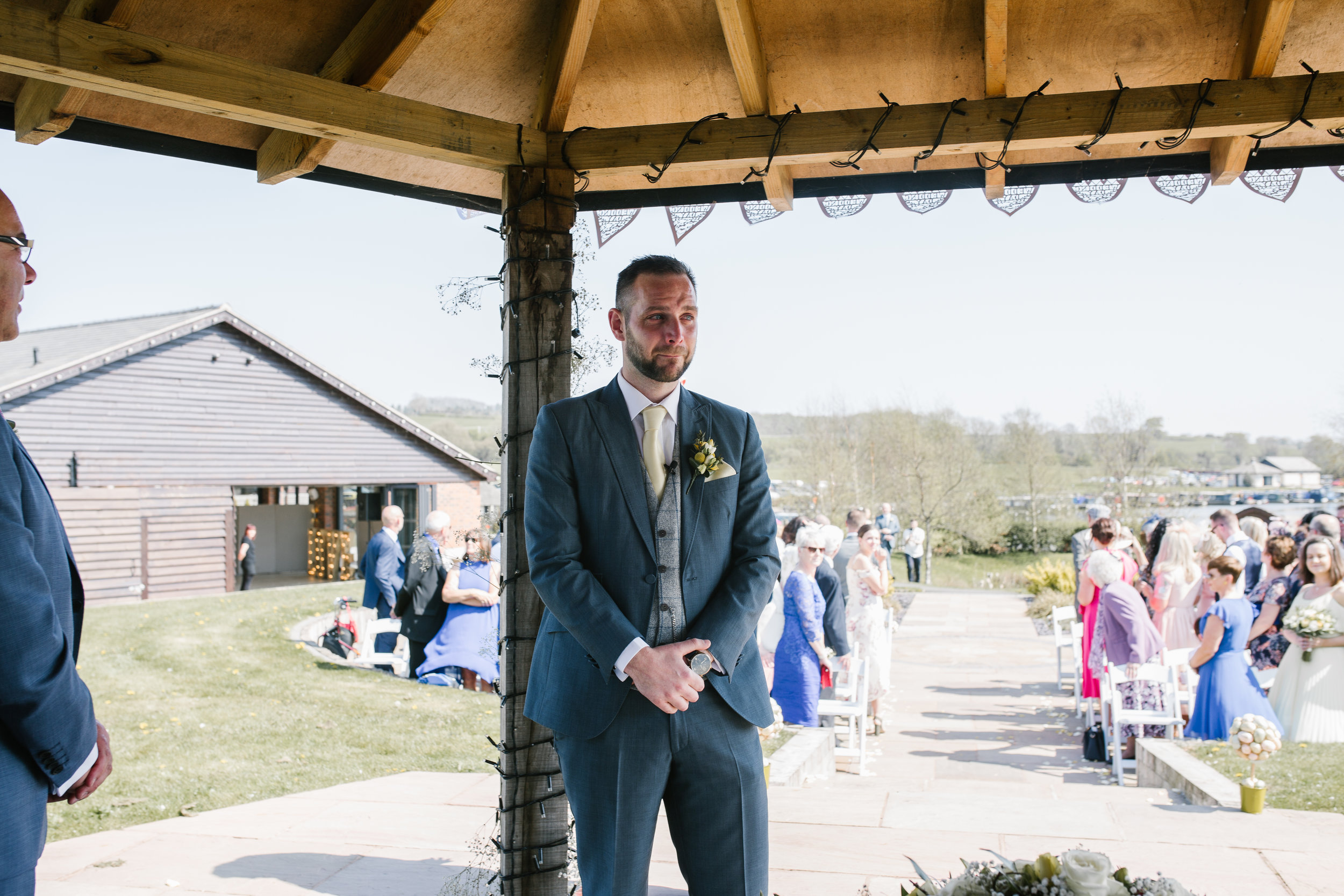 groom waiting for his bride at the outdoor wedding ceremony at the boat house staffordshire