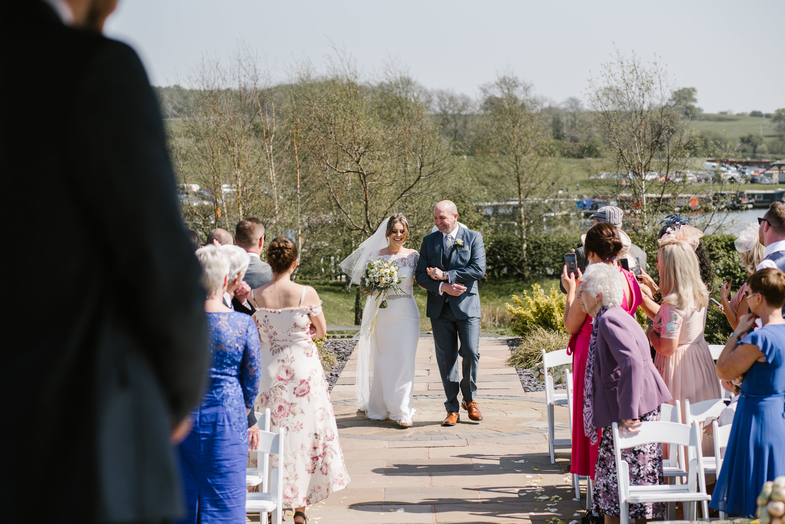 bride with her father walking down the aisle at her outdoor ceremony in aston marina staffordshire
