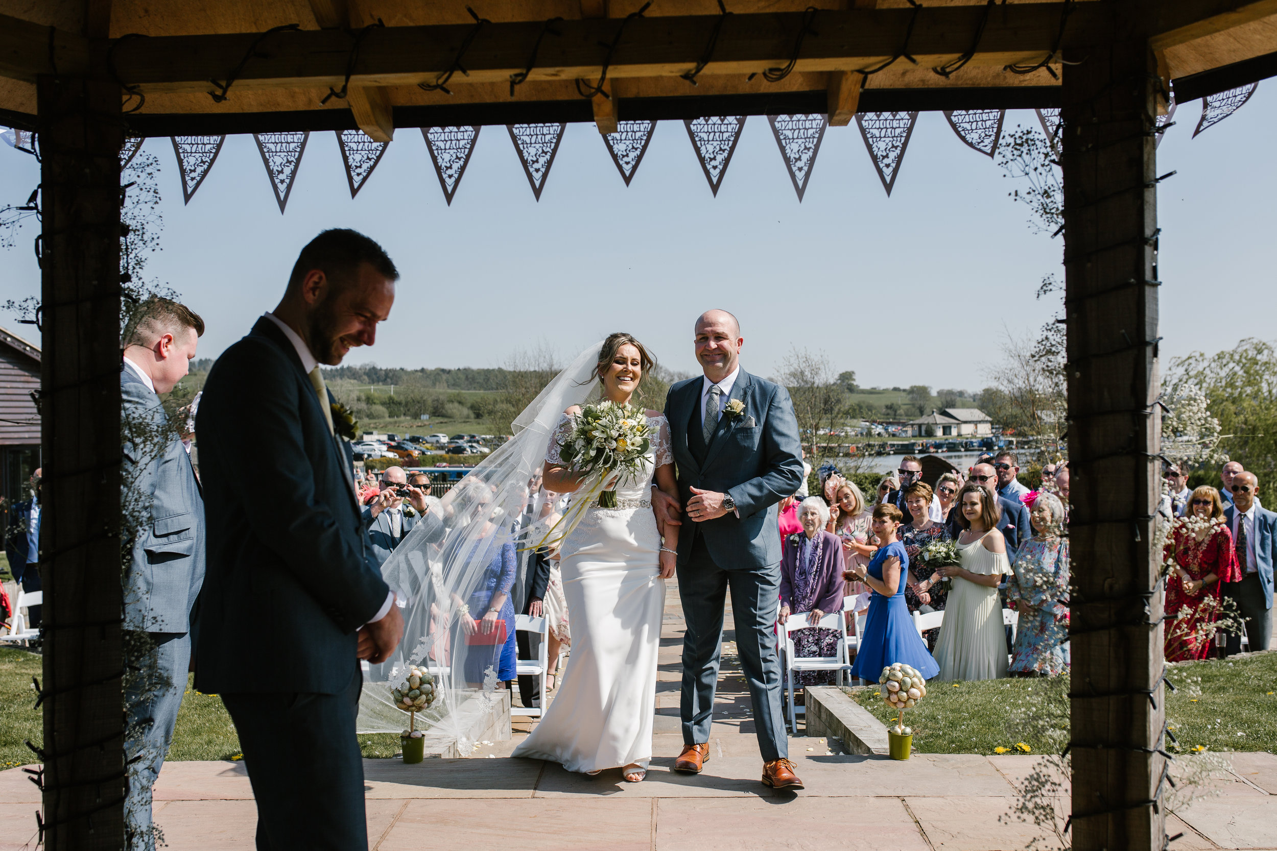 bride meeting her groom at the top of the aisle at their outdoor wedding ceremony