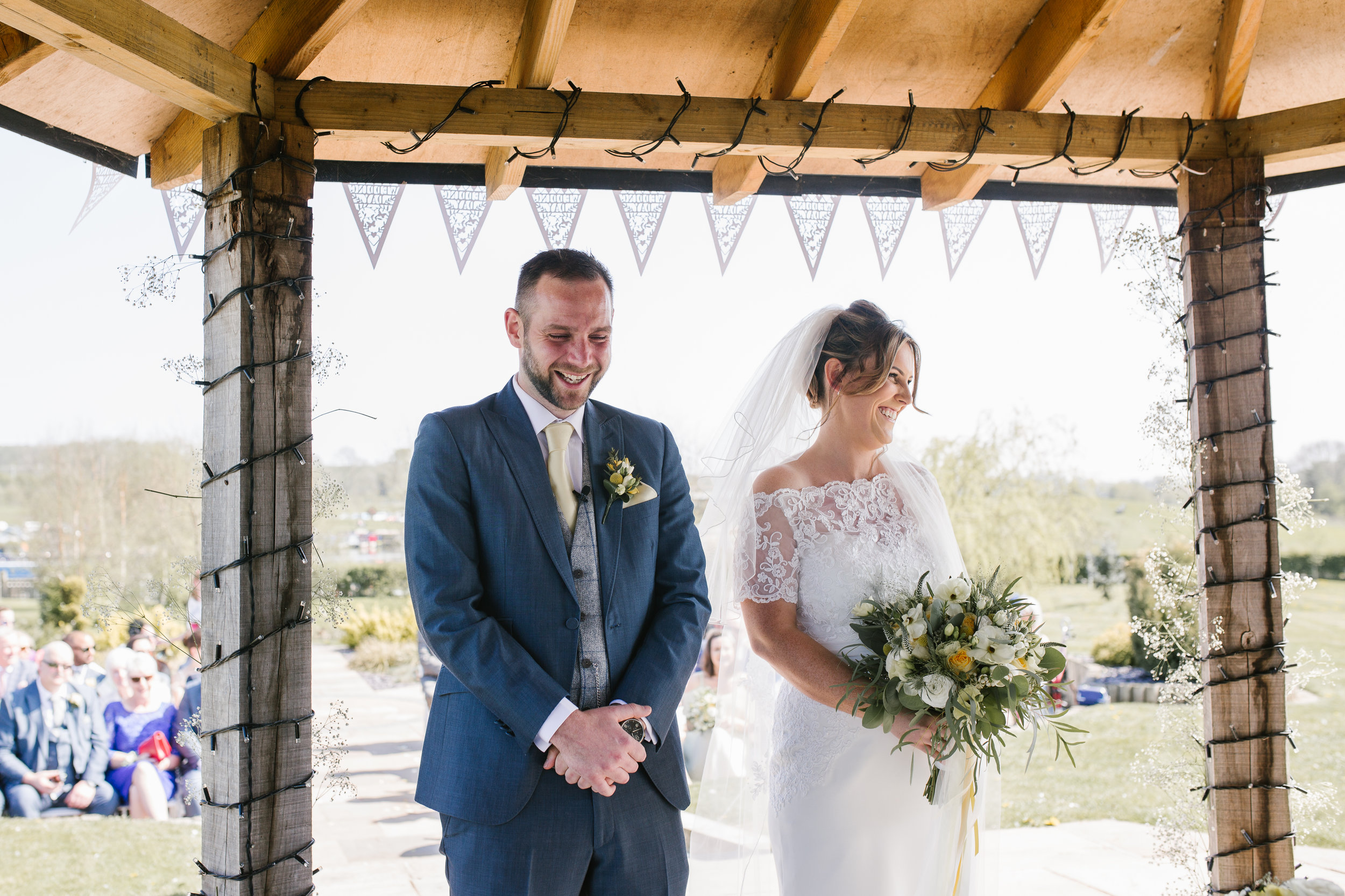bride and groom laughing and crying together at the top of the aisle