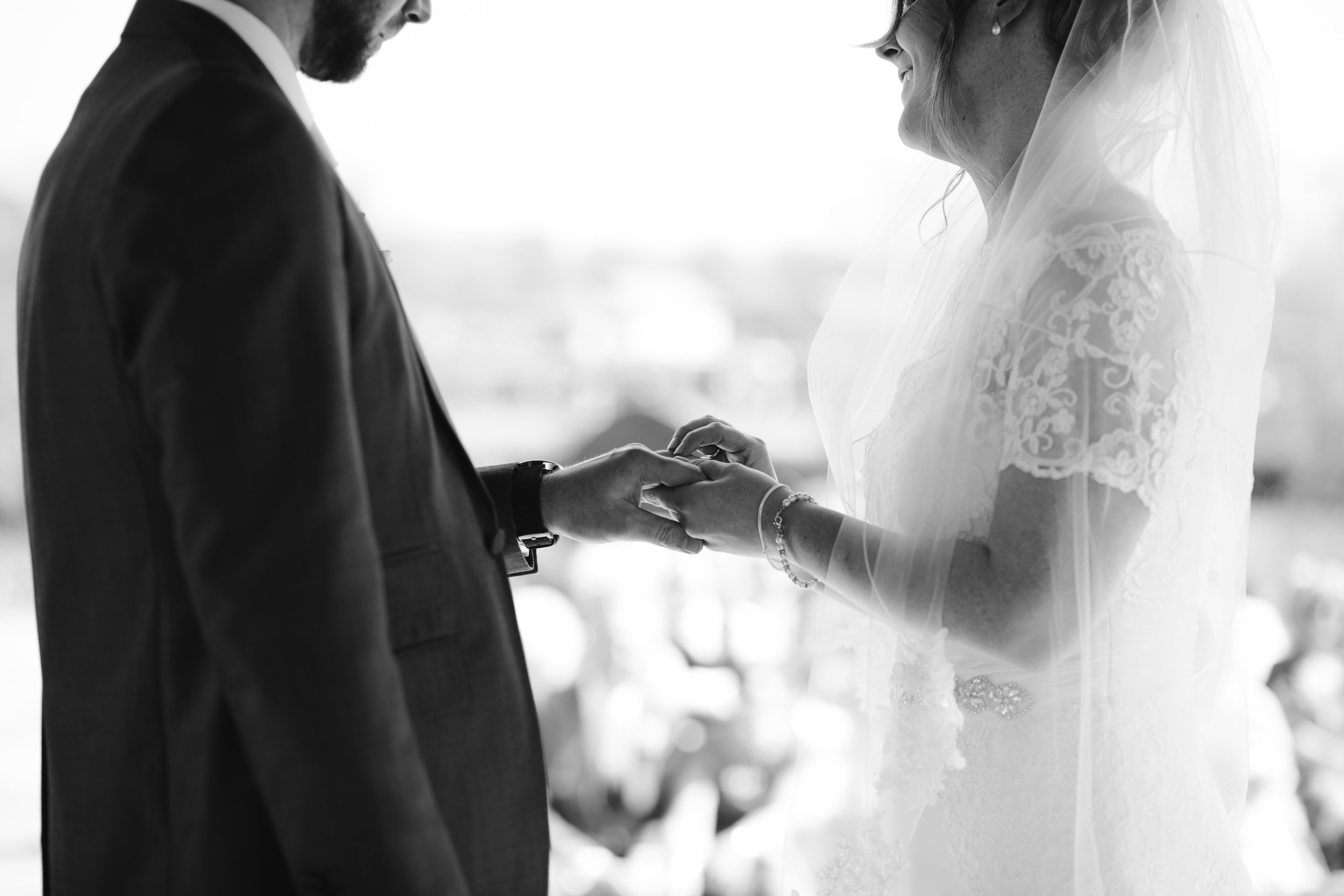 black and white detailed photo of the bride and groom exchanging rings