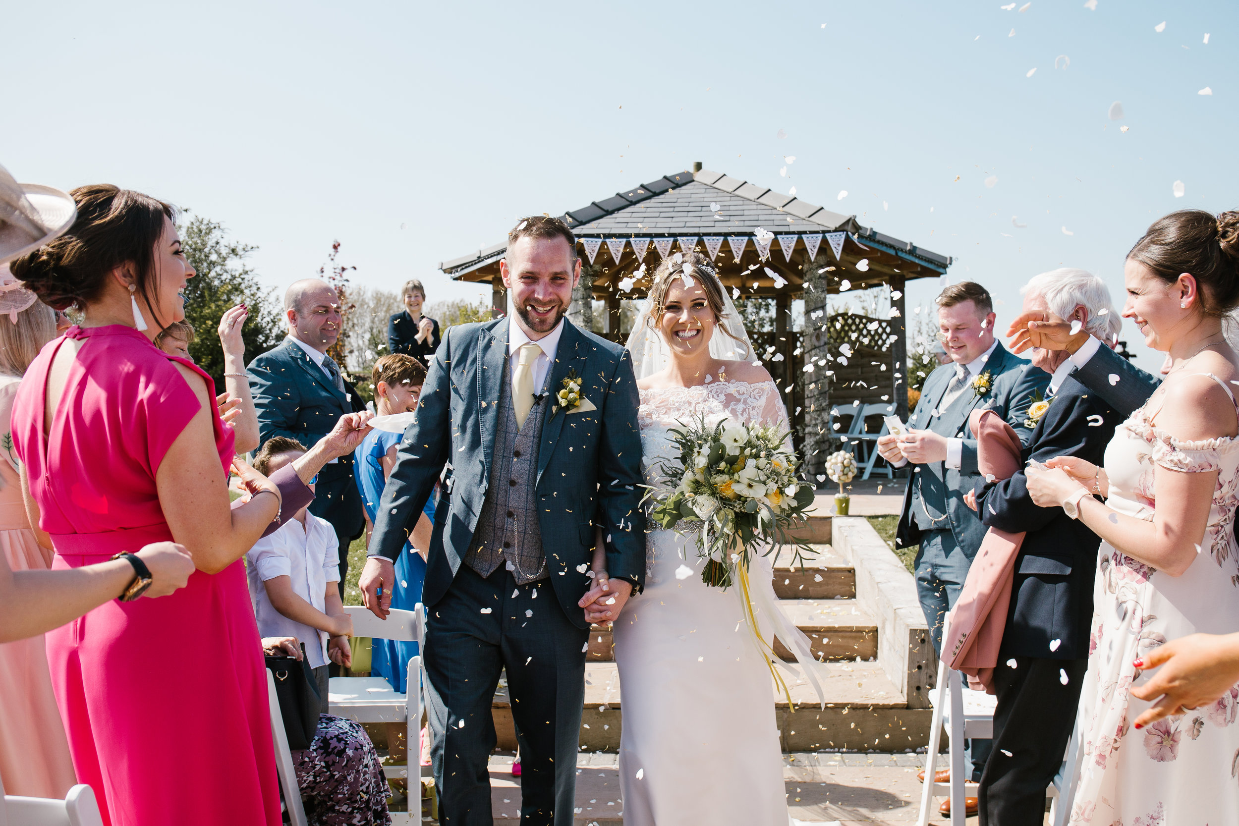 bride and groom laughing together as they walked down the aisle being showered in confetti after becoming husband and wife