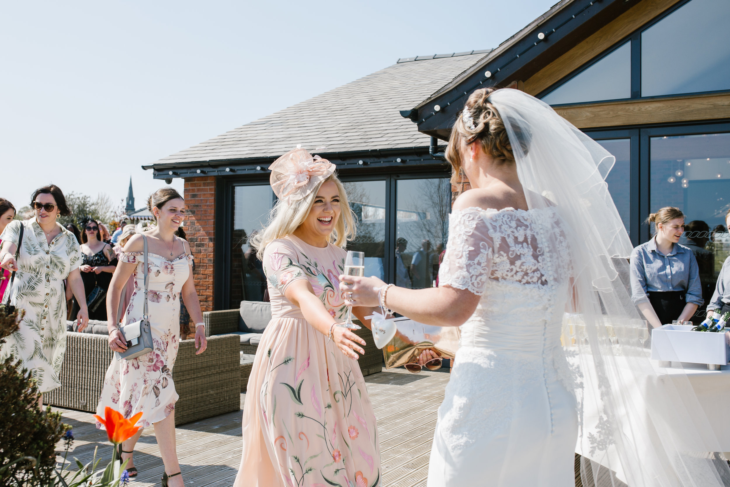 bride being greeted by her guests at her outdoor wedding in the boat house aston marina in staffordshire