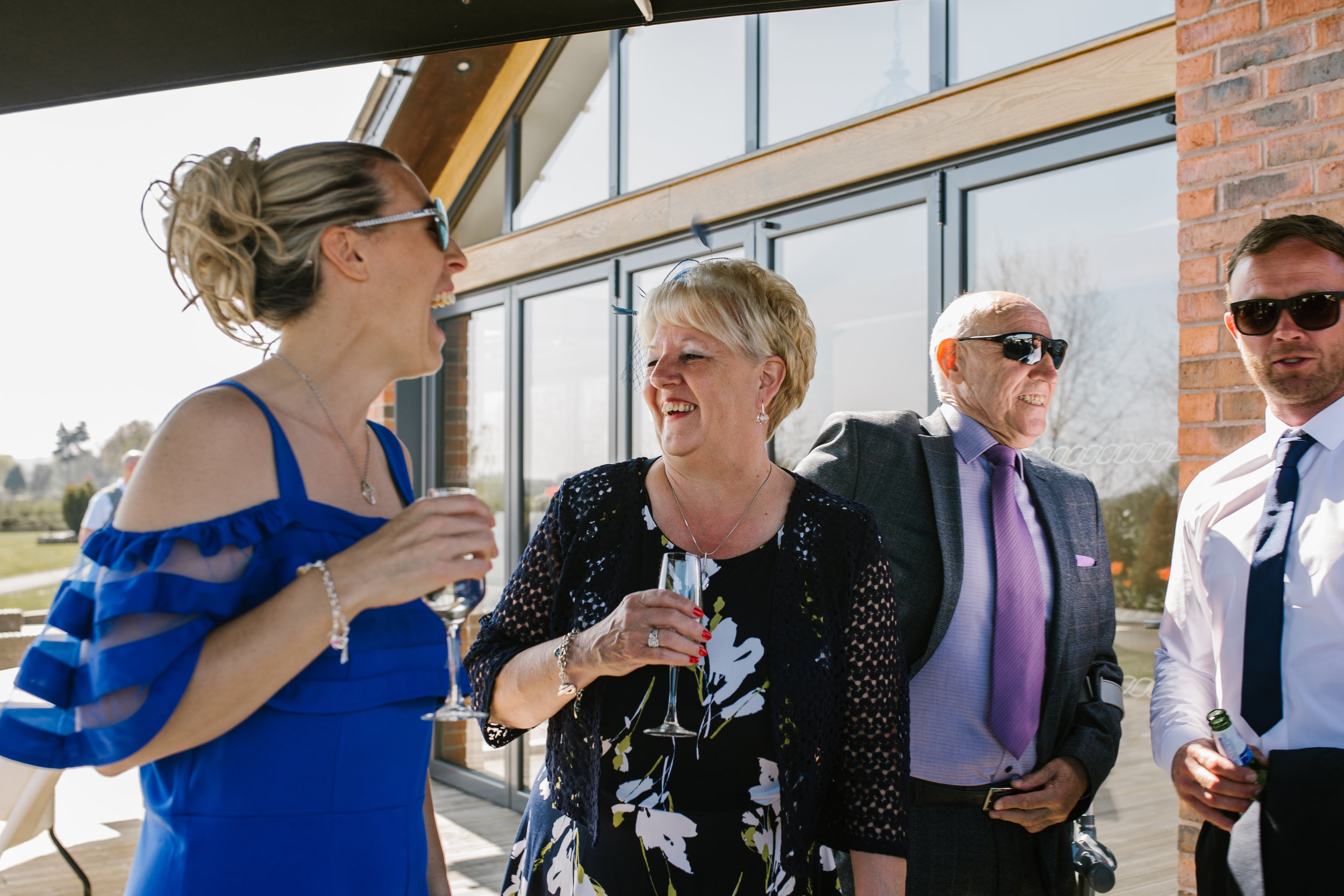 natural photograph of wedding guests laughing together at the boat house aston marina