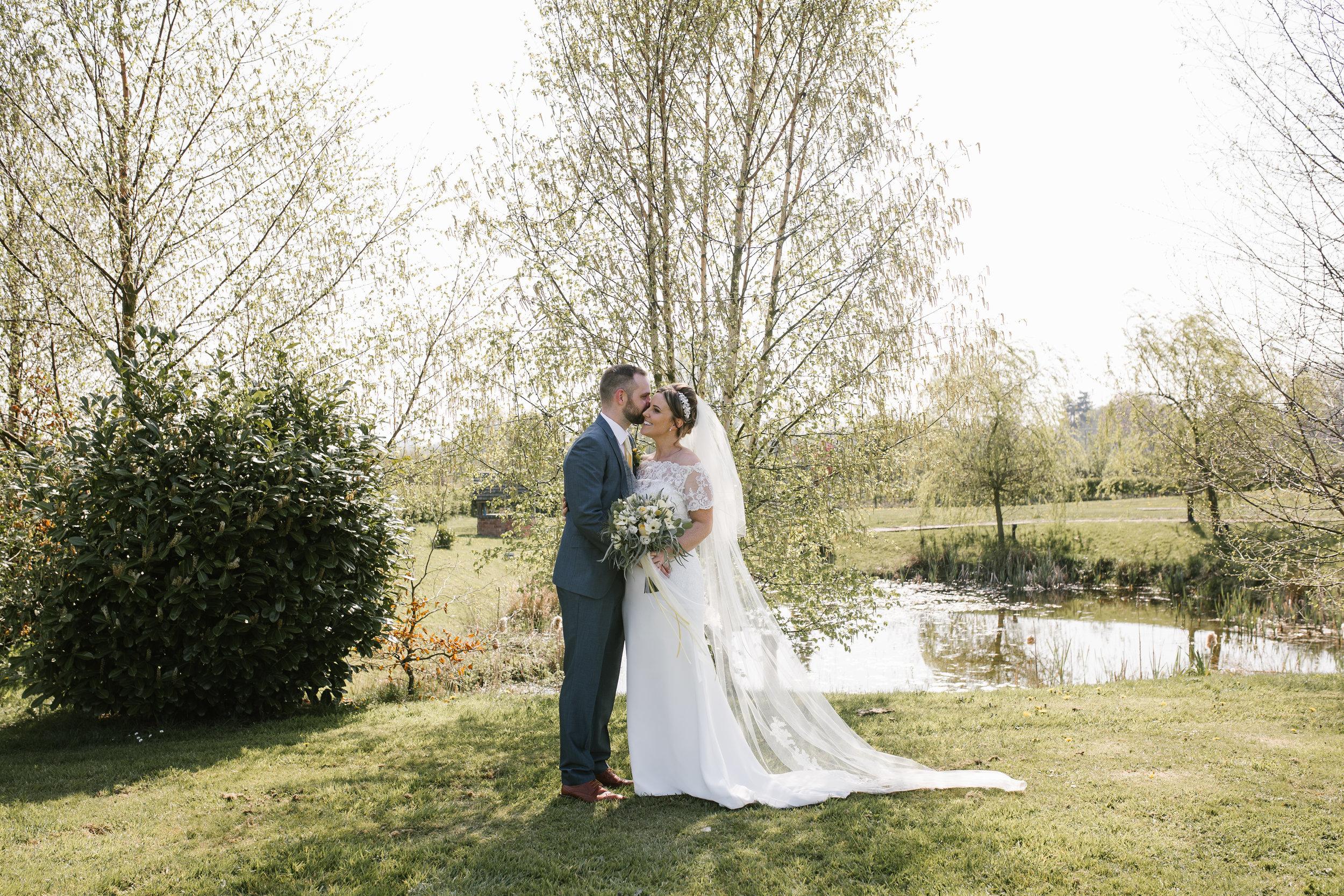 groom whispering into his brides ear at aston marina boat house wedding venue