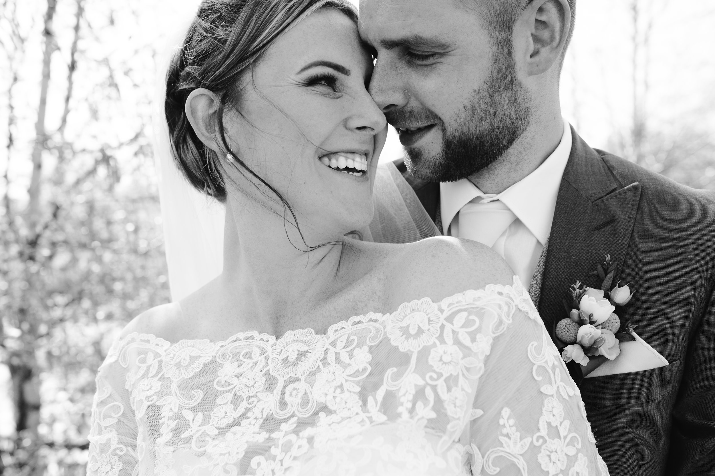 black and white photo of bride and groom snuggling together at their wedding in staffordshire