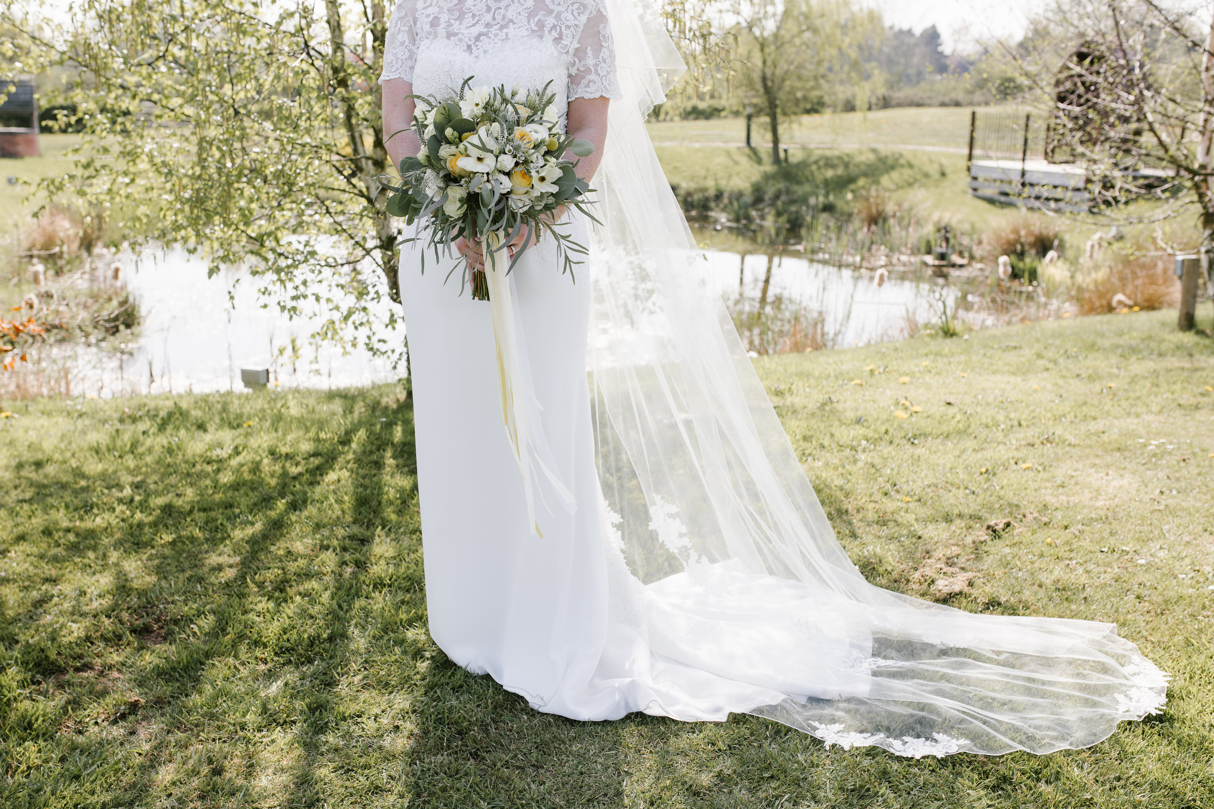 deatil photo of wedding florals and brides dress in the summer light
