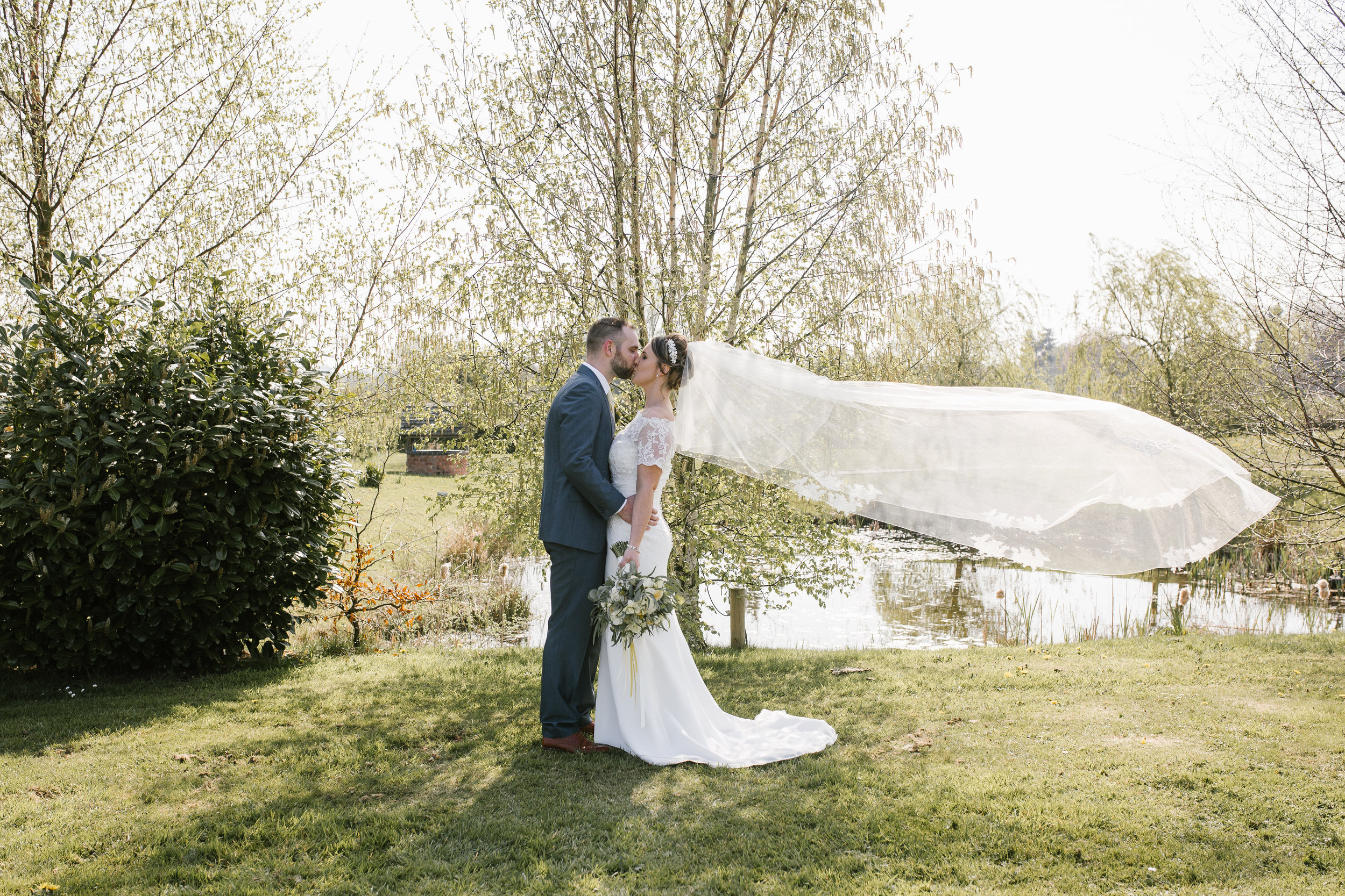 bride and groom kiss as the brides veil floats in the wind- wedding at the boat house at aston marina