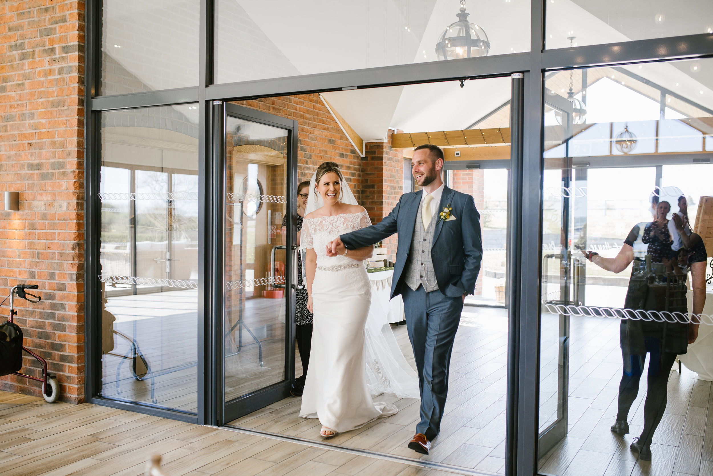 bride and groom make an entrance into the wedding breakfast and get cheered into the room by their guests