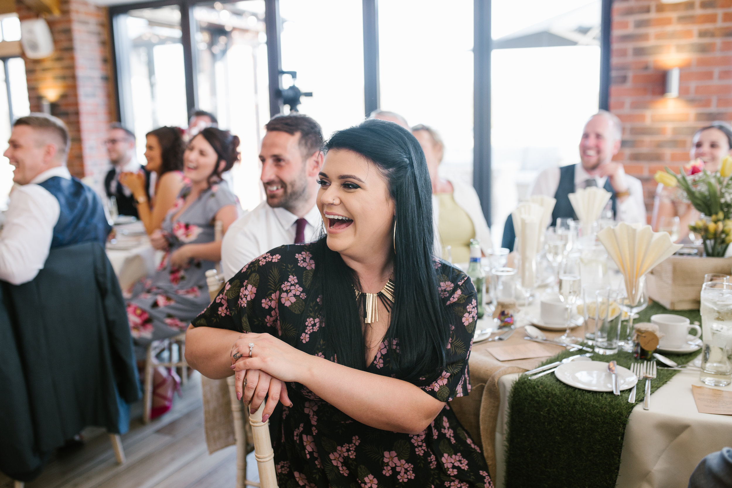 wedding guests laughing during father of the bride speech at the boat house wedding venue