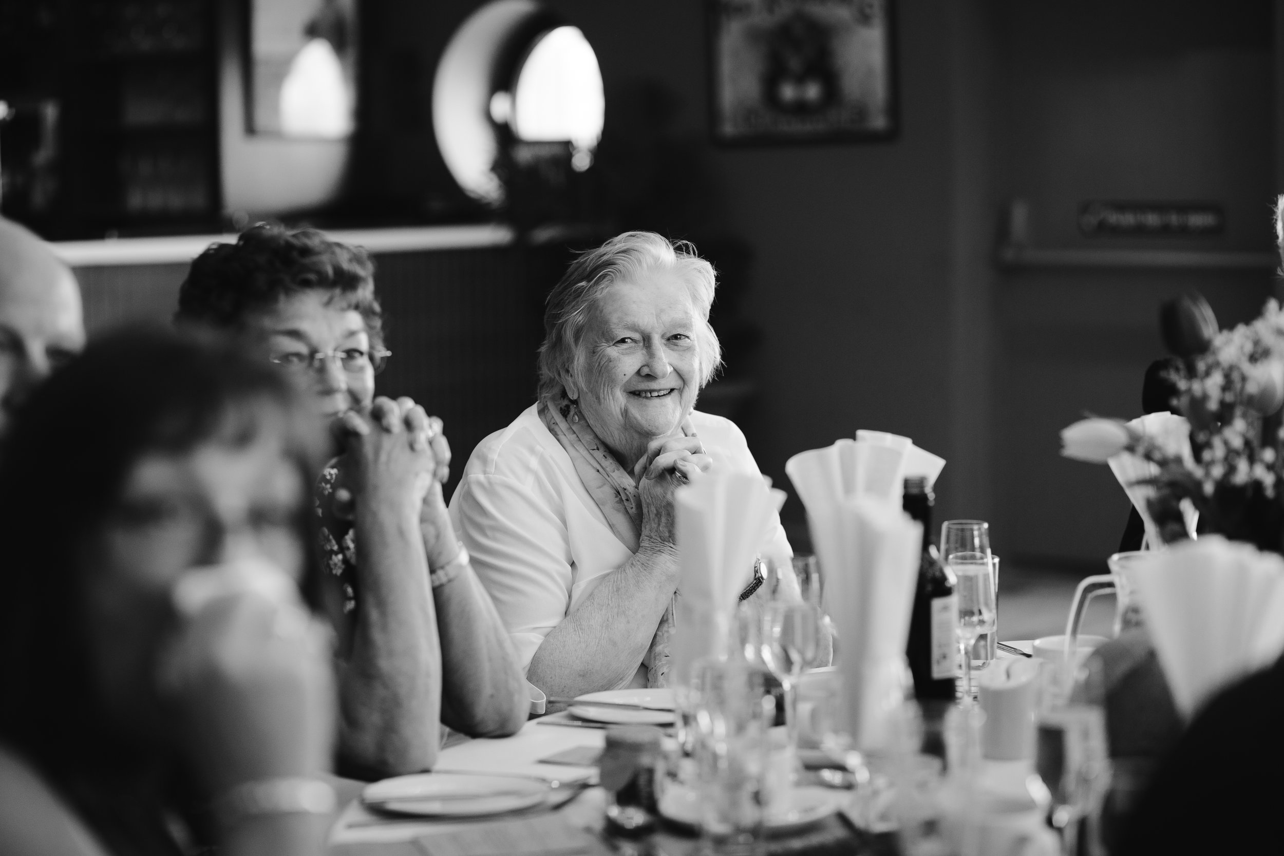 black and white photo of nan smiling during the wedding speeches