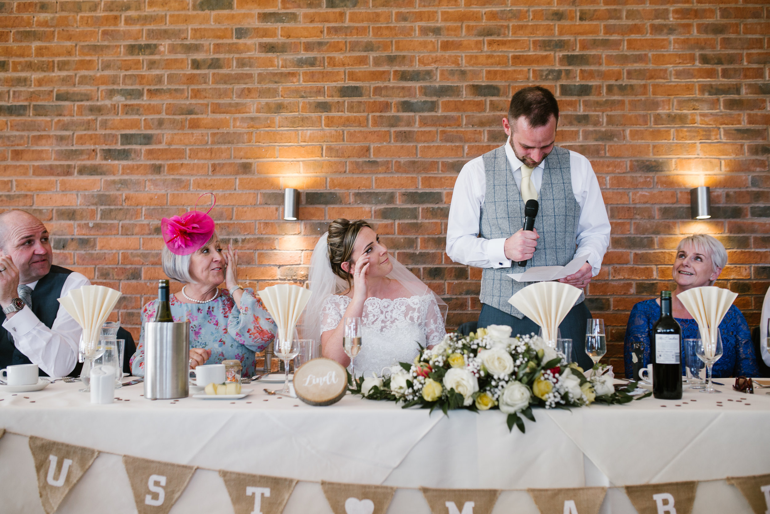 groom reading his speech while his new bride cries