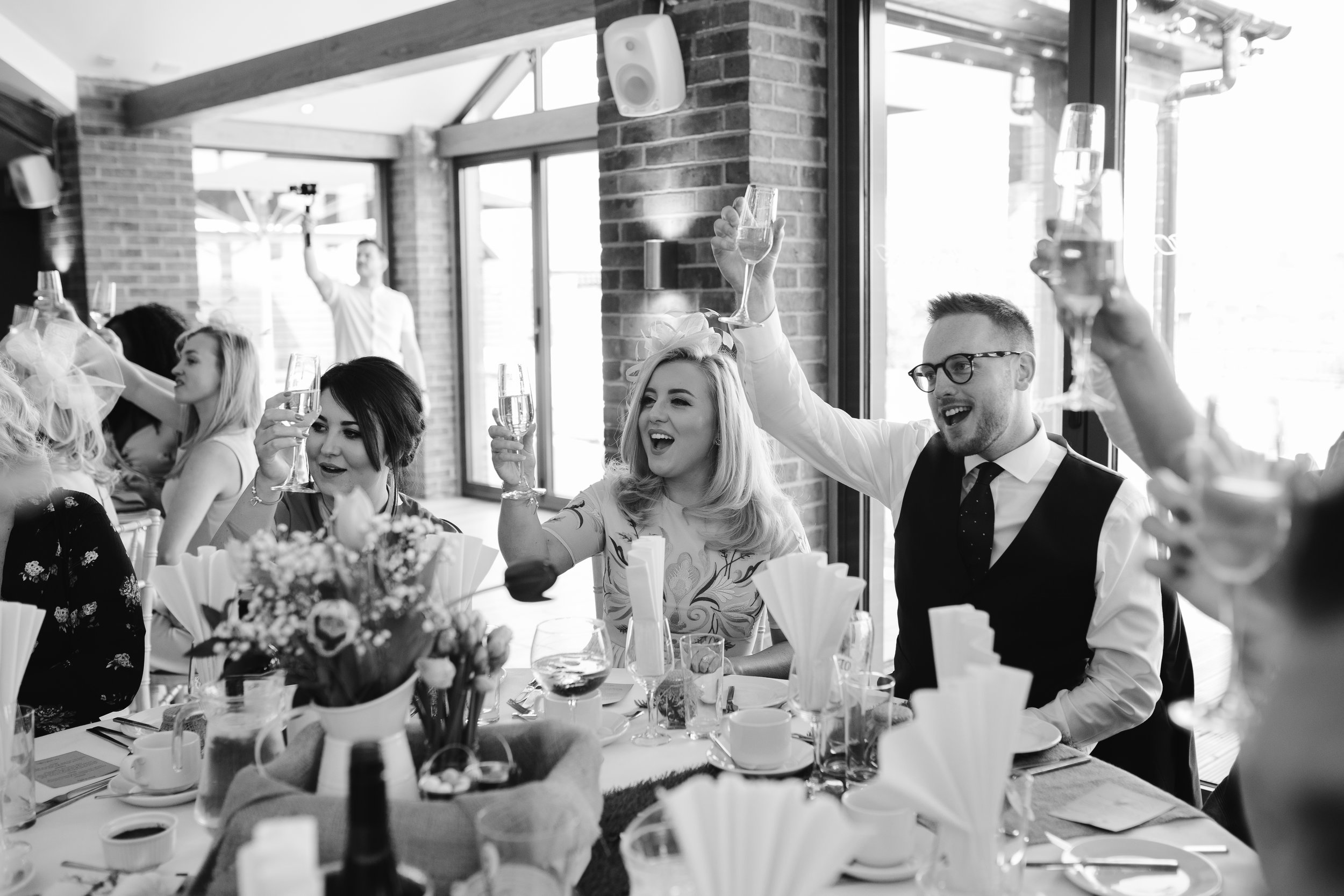 black and white photo of wedding gets cheering during the wedding speeches