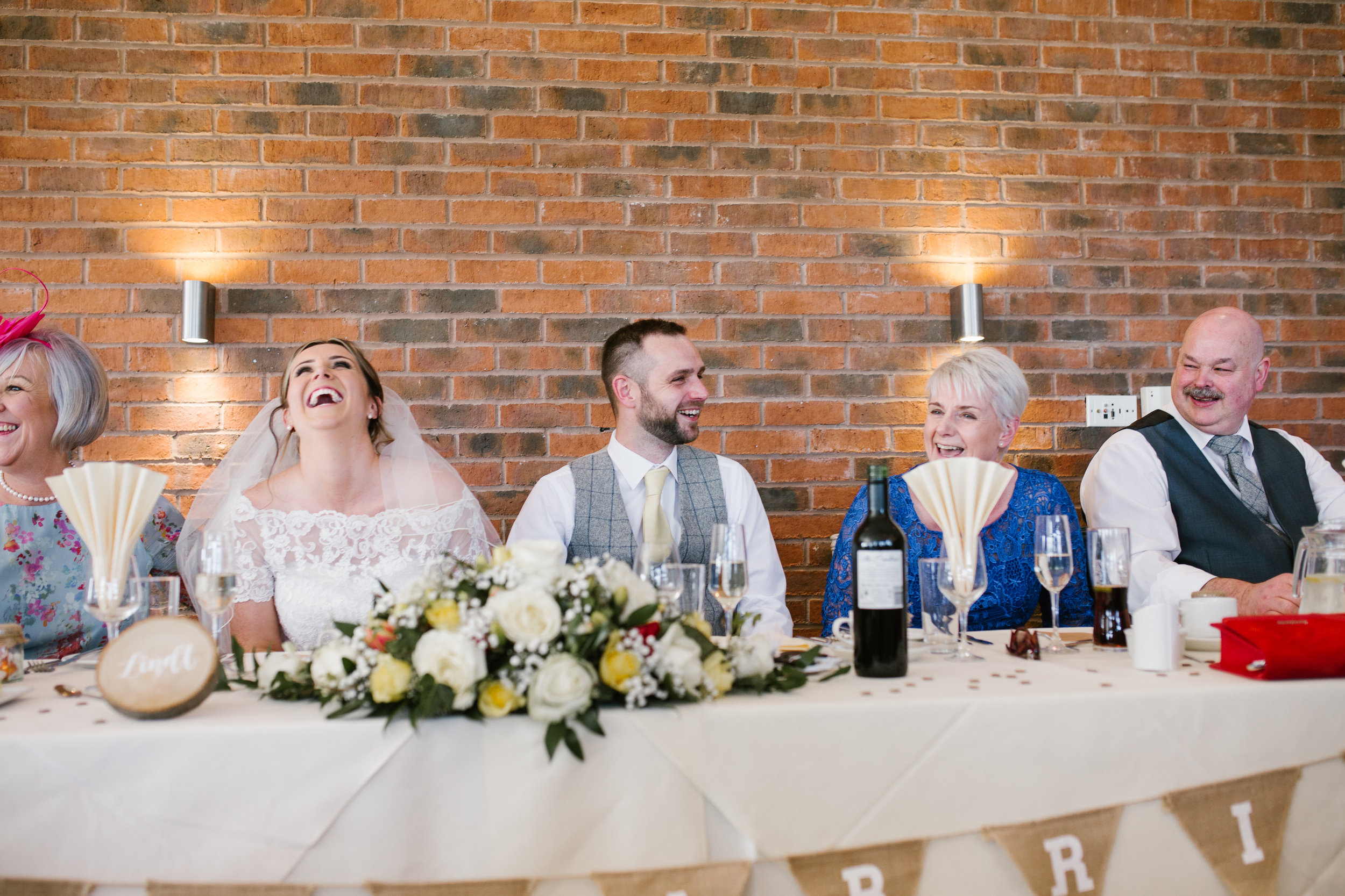the top tabel laughing together during the wedding speeches