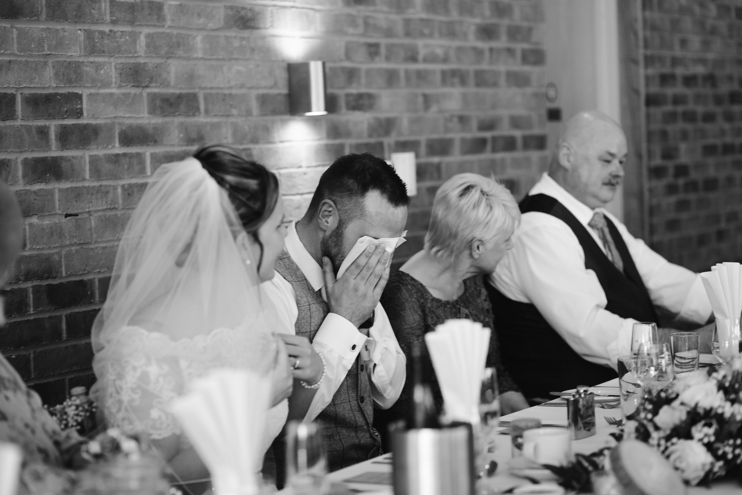 black and white photo of the groom crying during the best man speech