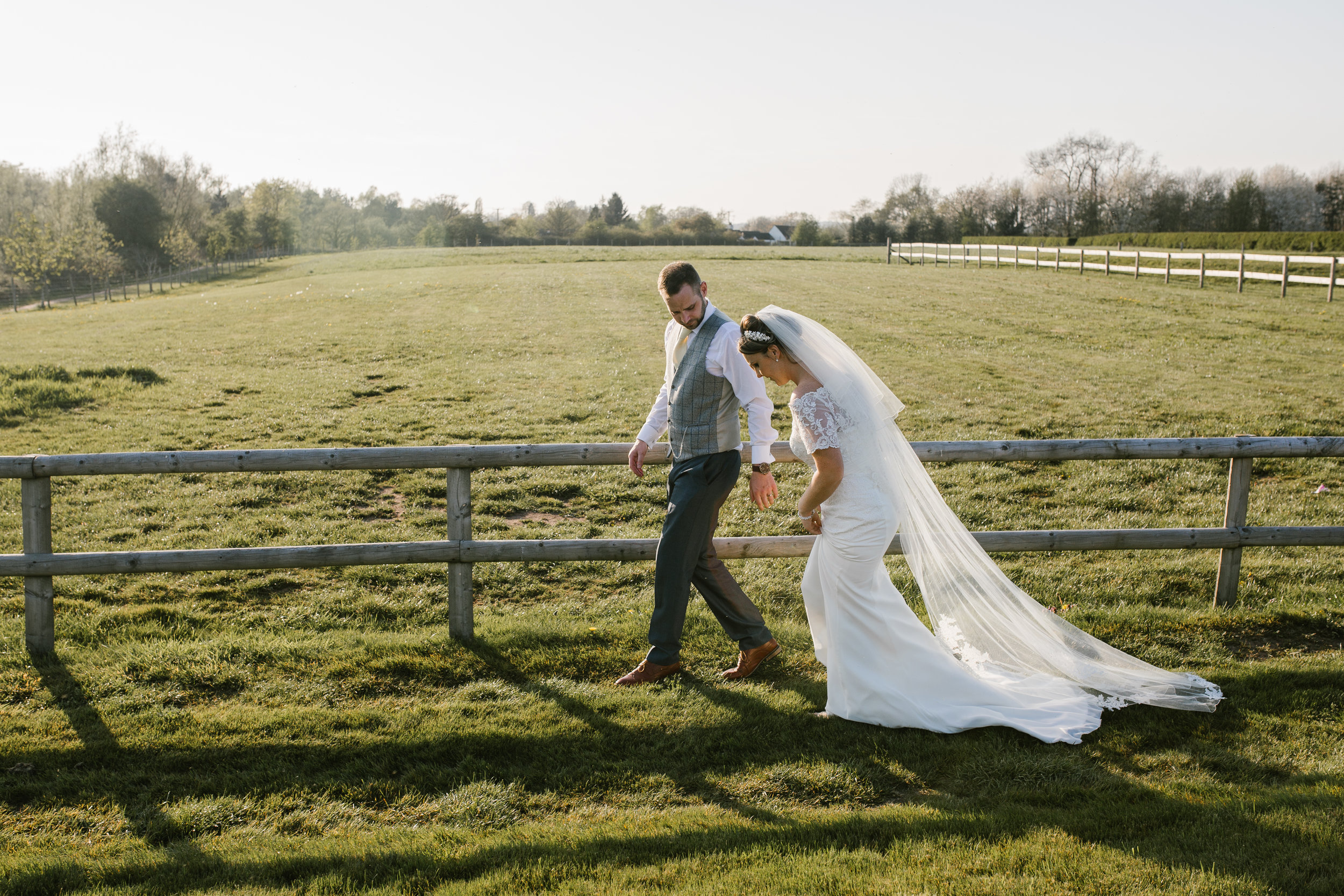 bride and groom strolling through a field together at golden hour