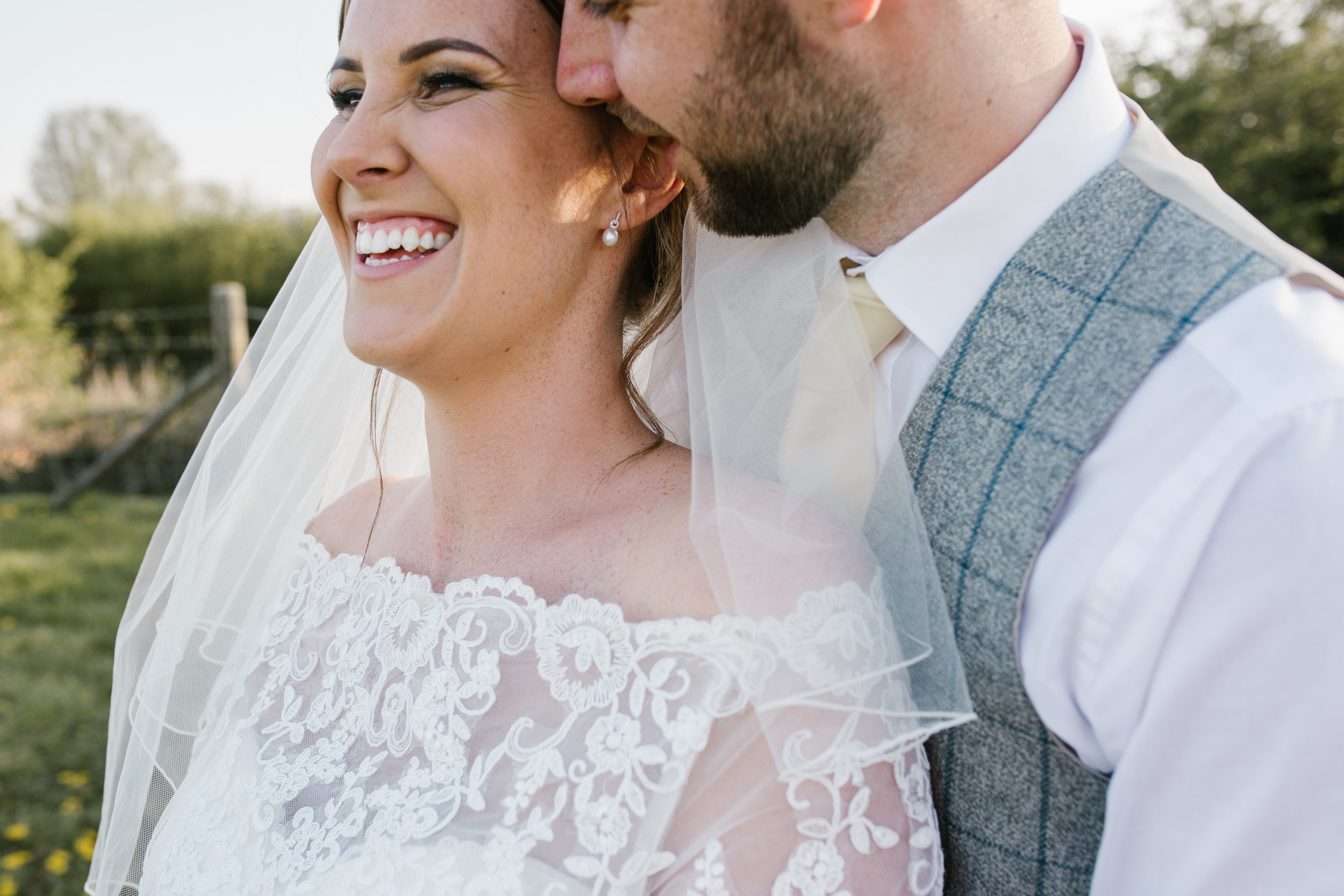 groom whispering into brides ear during golden hour