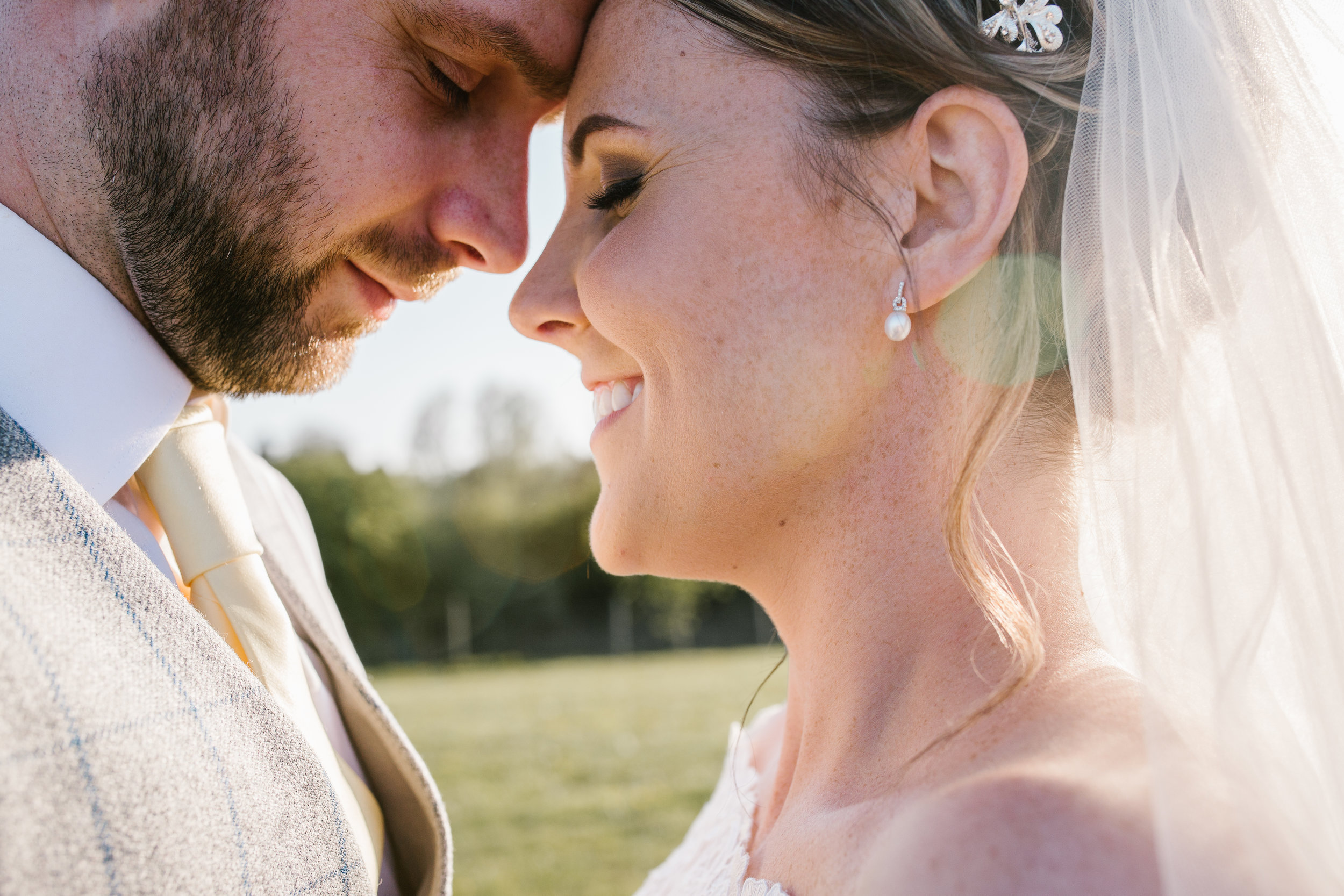 close up photo of bride and groom smiling at one another