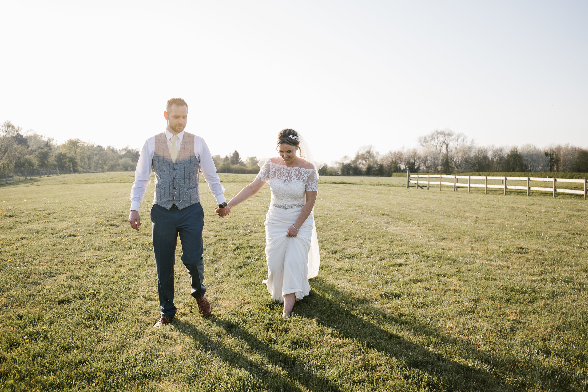 bride and groom walking hand in hand through a field