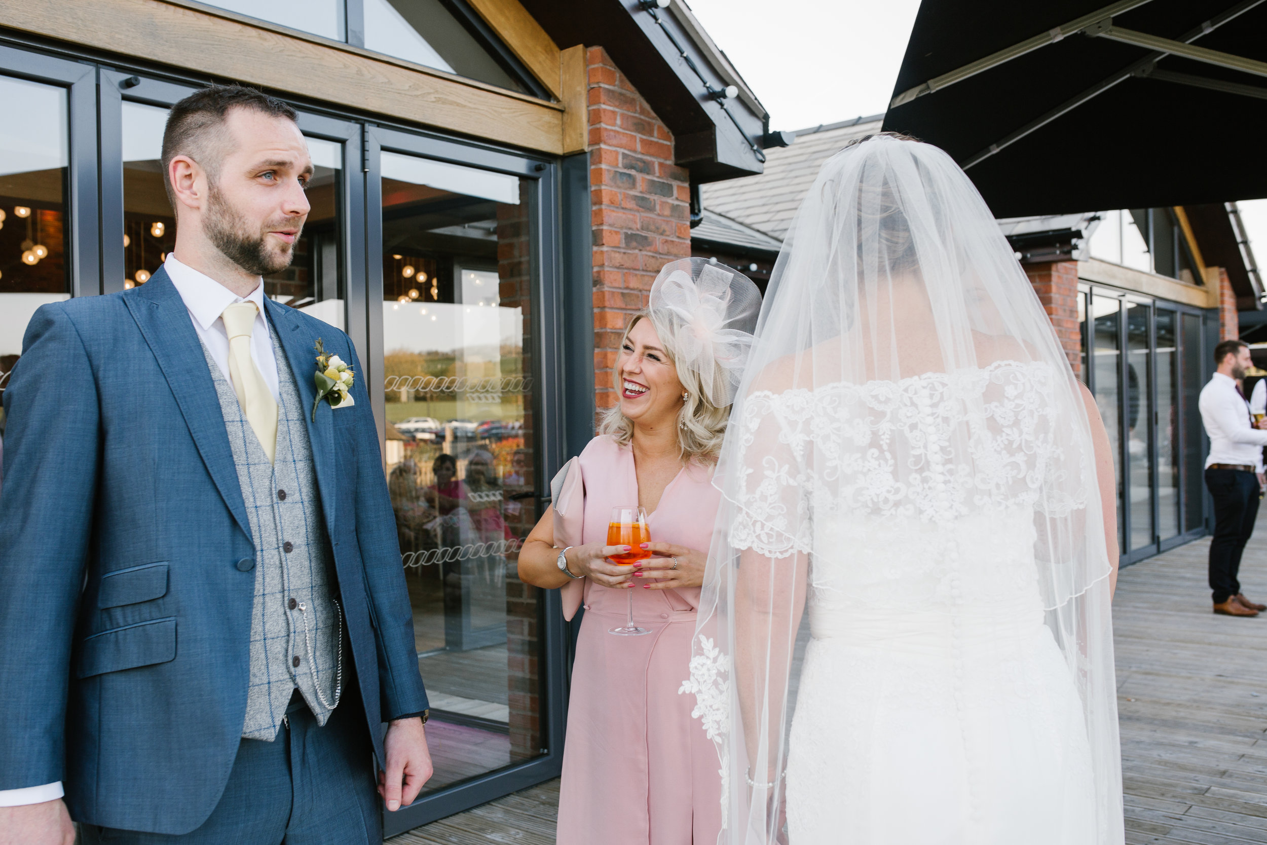 groom greeted wedding guests as they drink on the evening of their wedding at the boat house