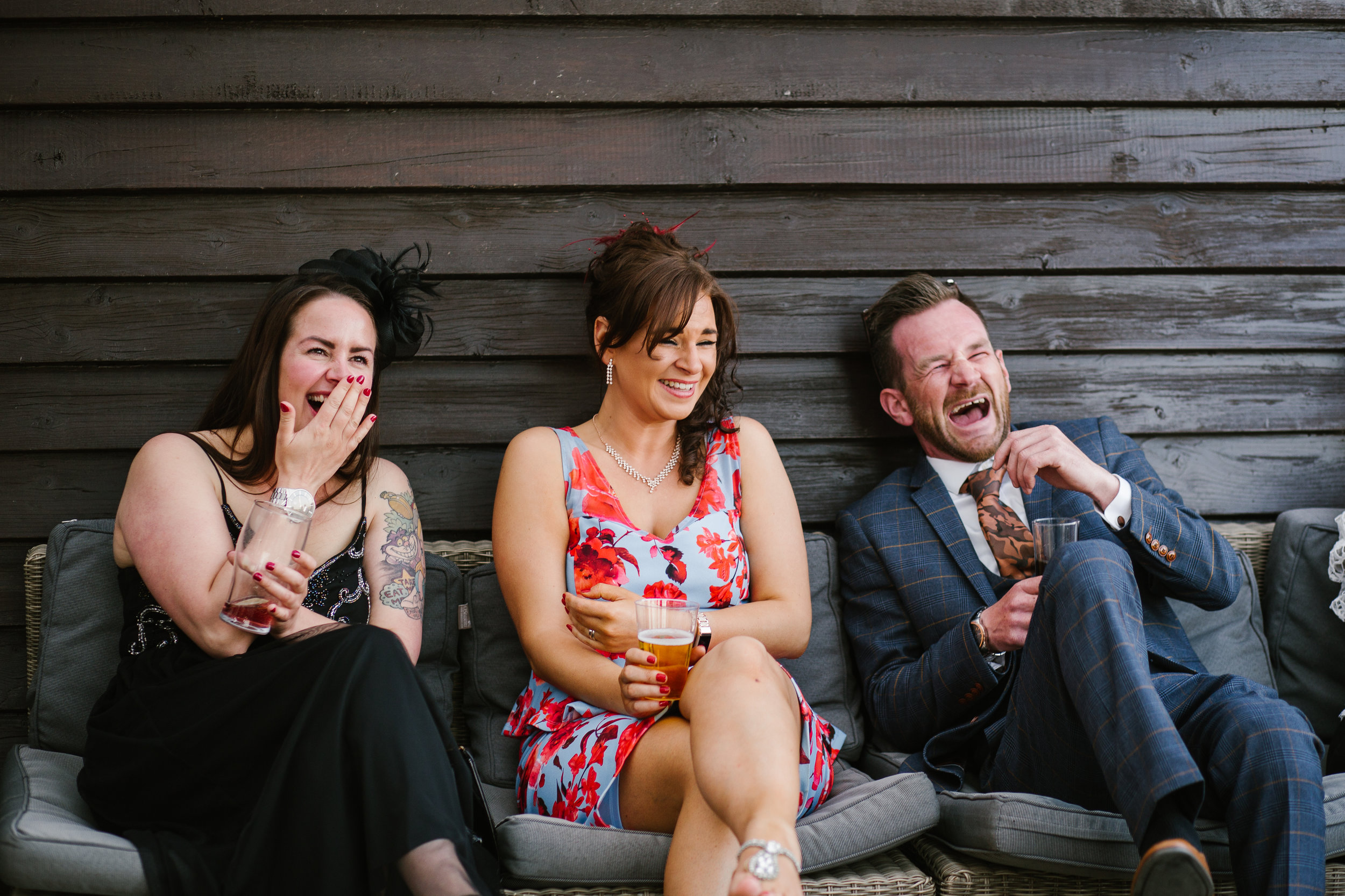 wedding guests laughing together while they have a drink on the patio at the boat house