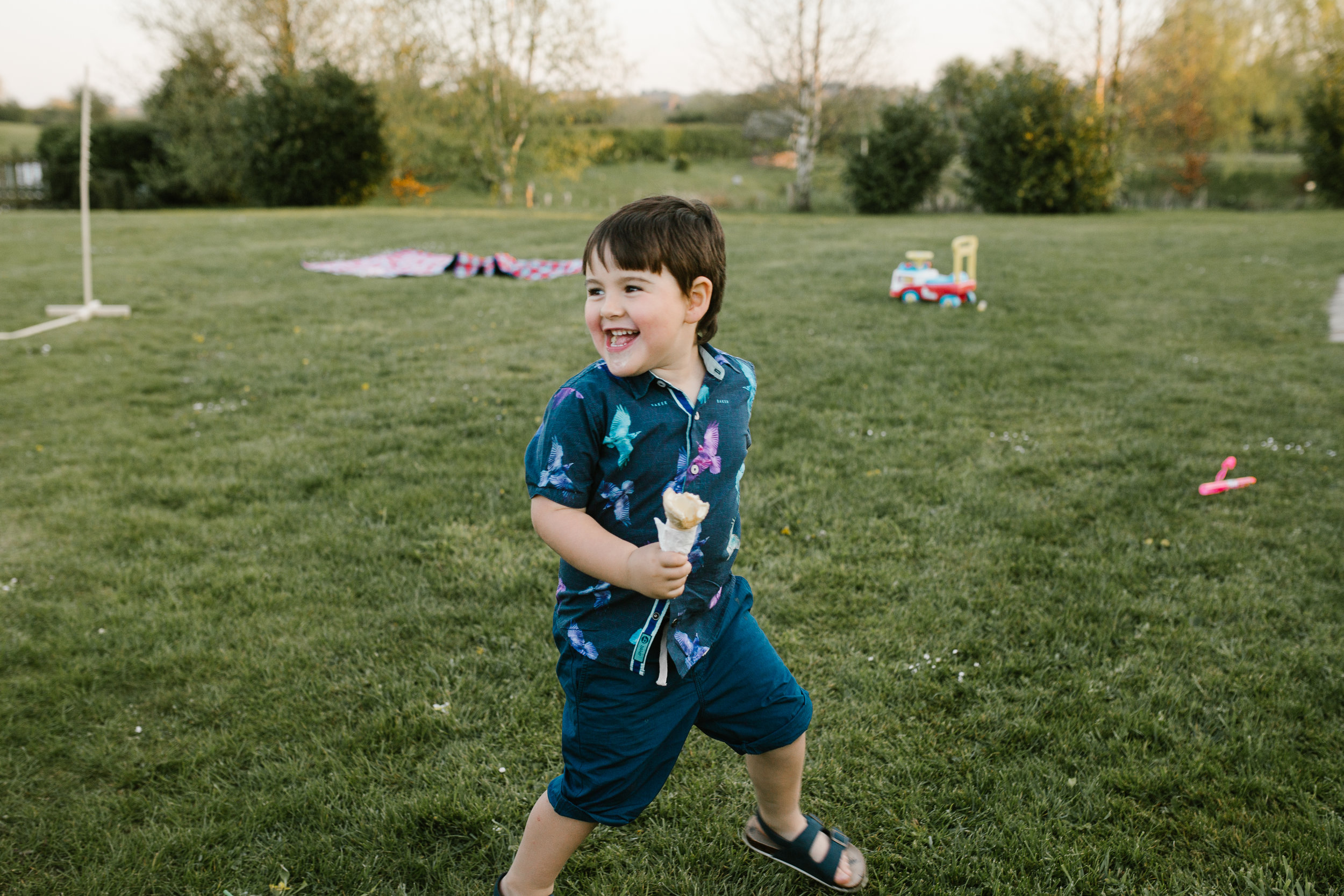 a boy at a wedding running around at the boat house
