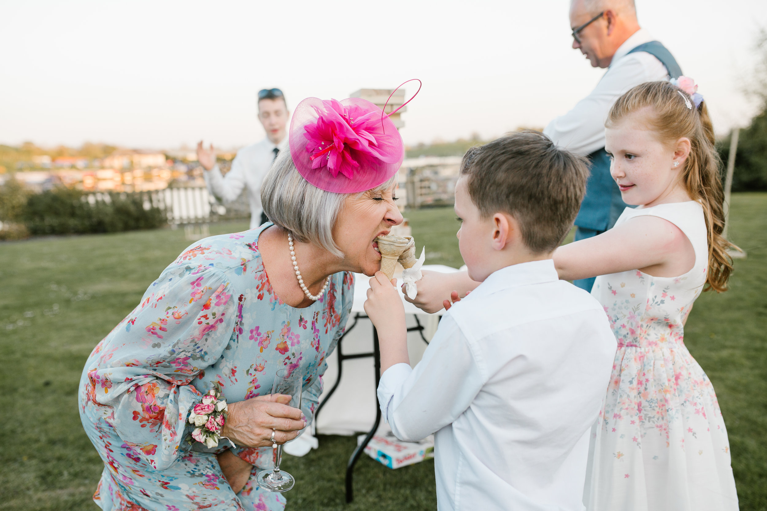 children at a wedding feed ice cream to the mother of the bride