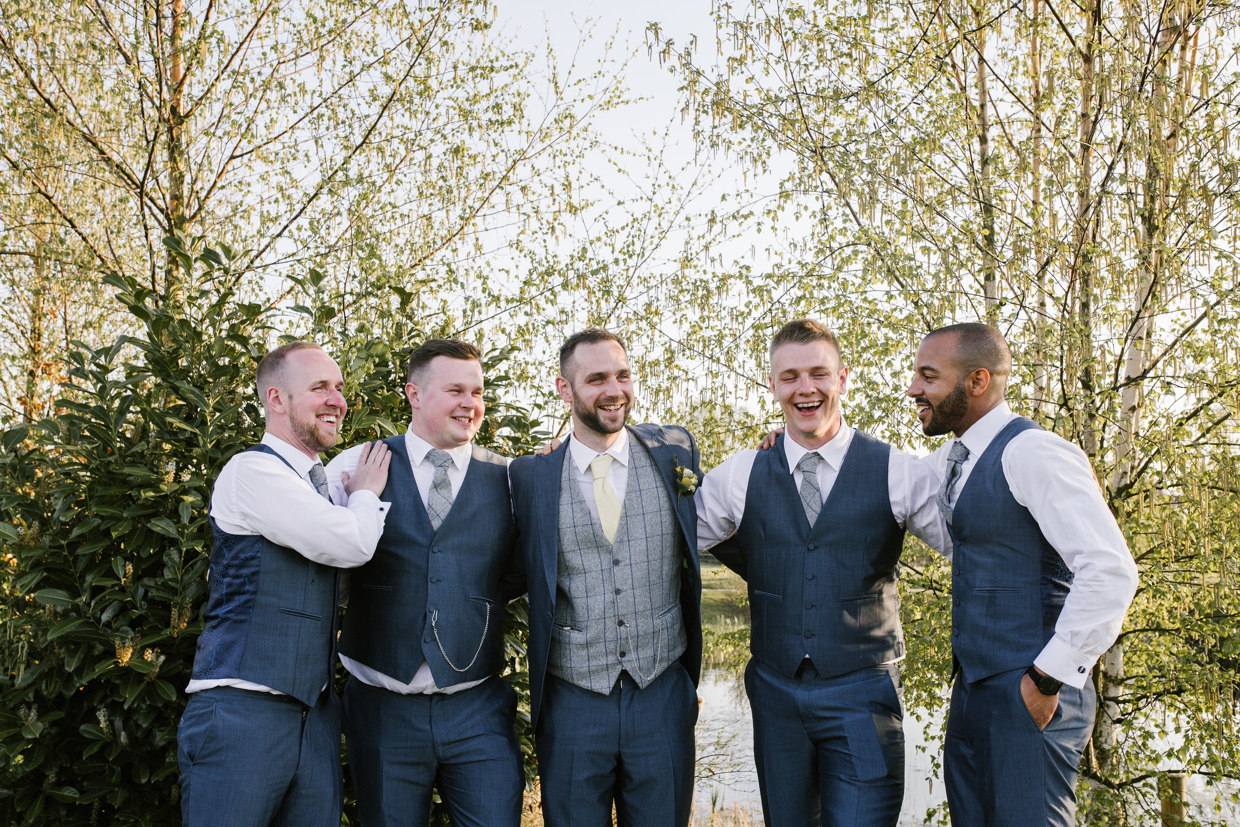 Groom with his groomsmen laughing together at the boat house in aston marina