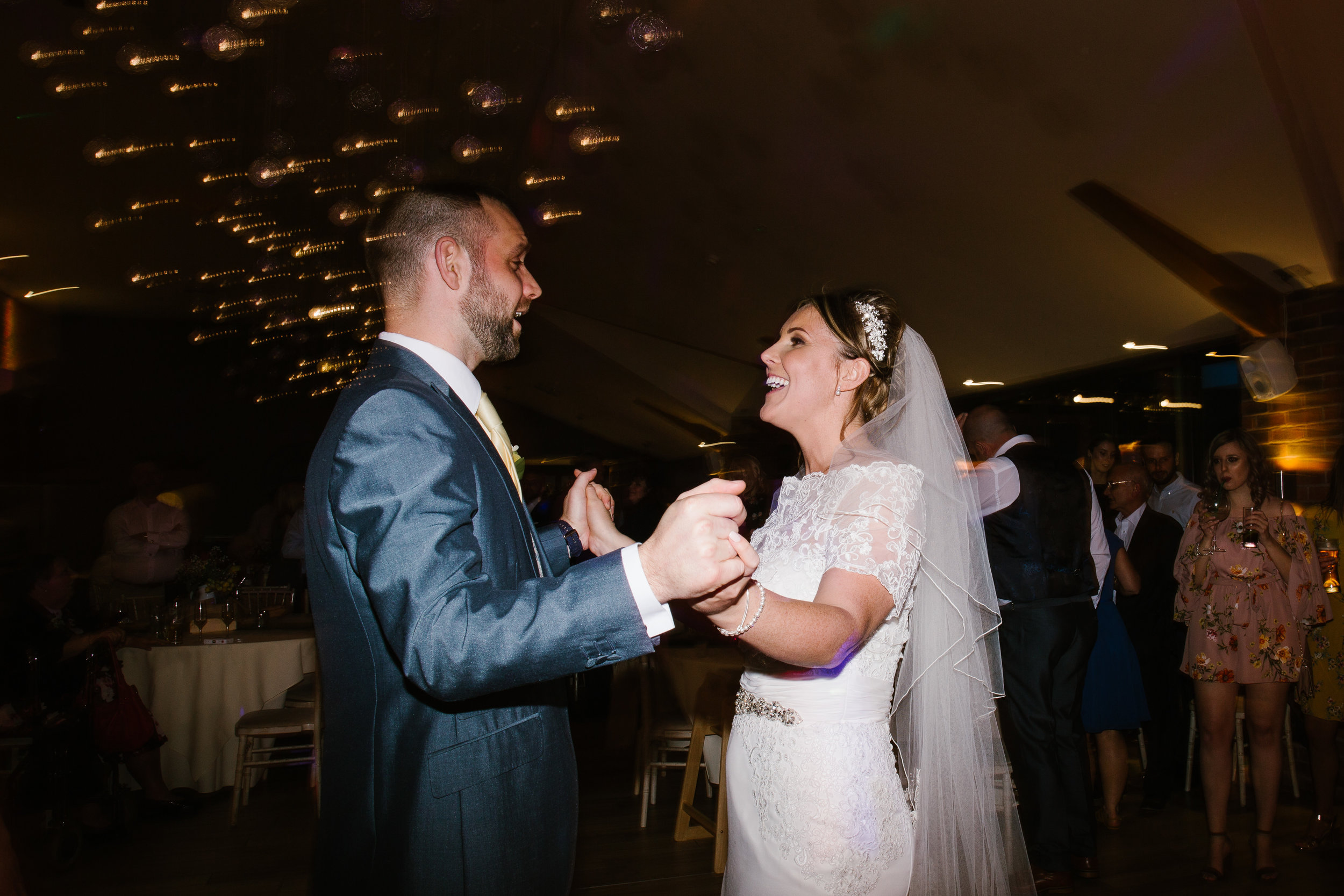 bride and groom laughing and dancing together at their spring wedding in staffordshire