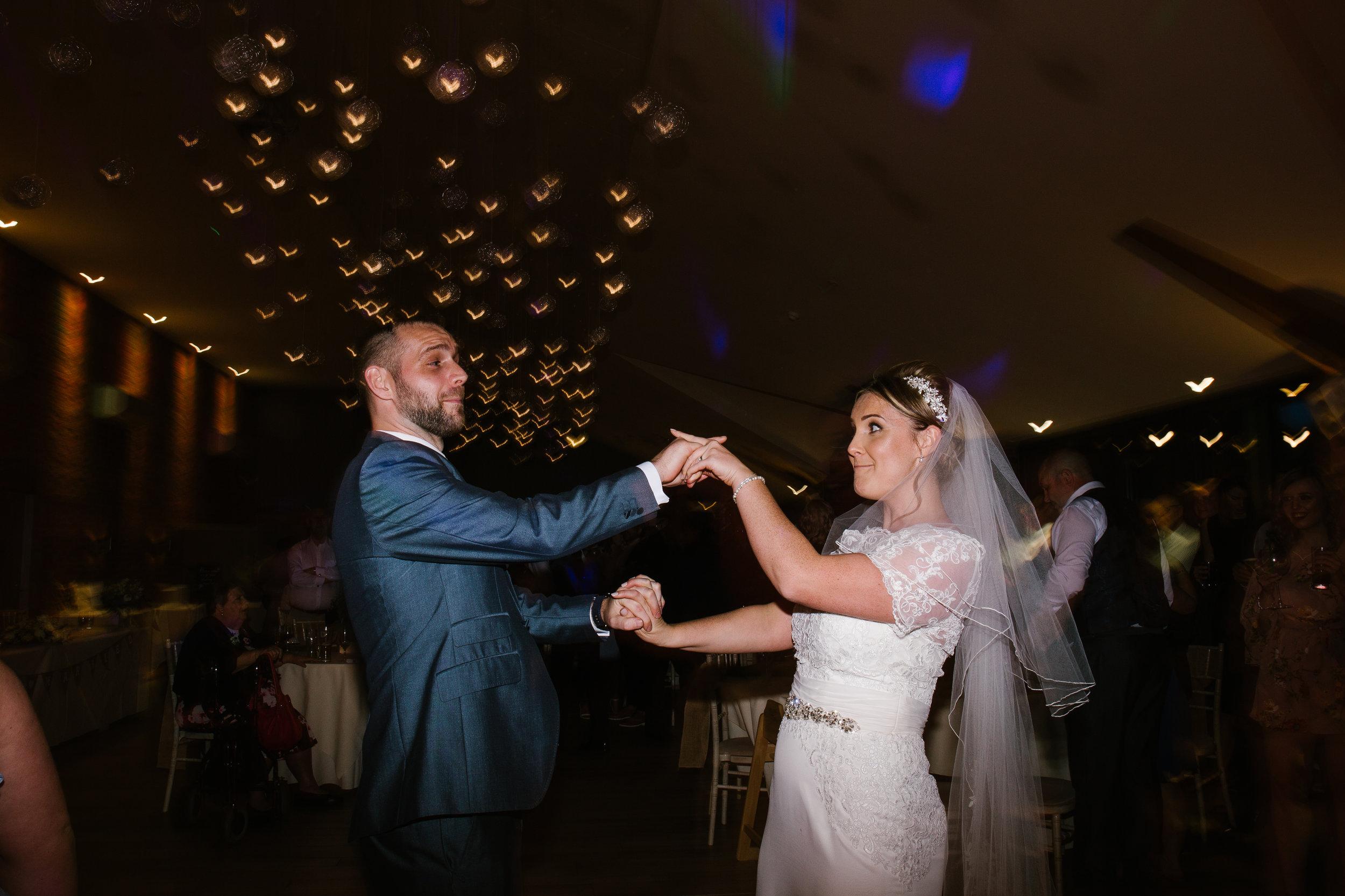 newlyweds dancing together at their fun wedding at aston marina