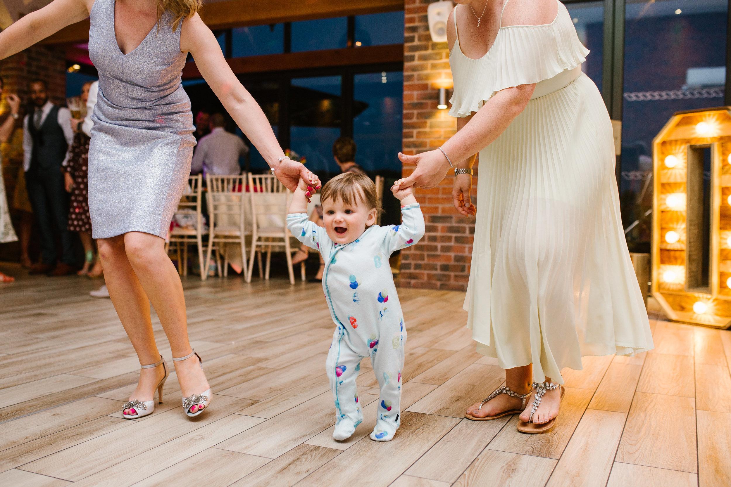 little toddler dancing in his onesie on the dance floor at aston marina