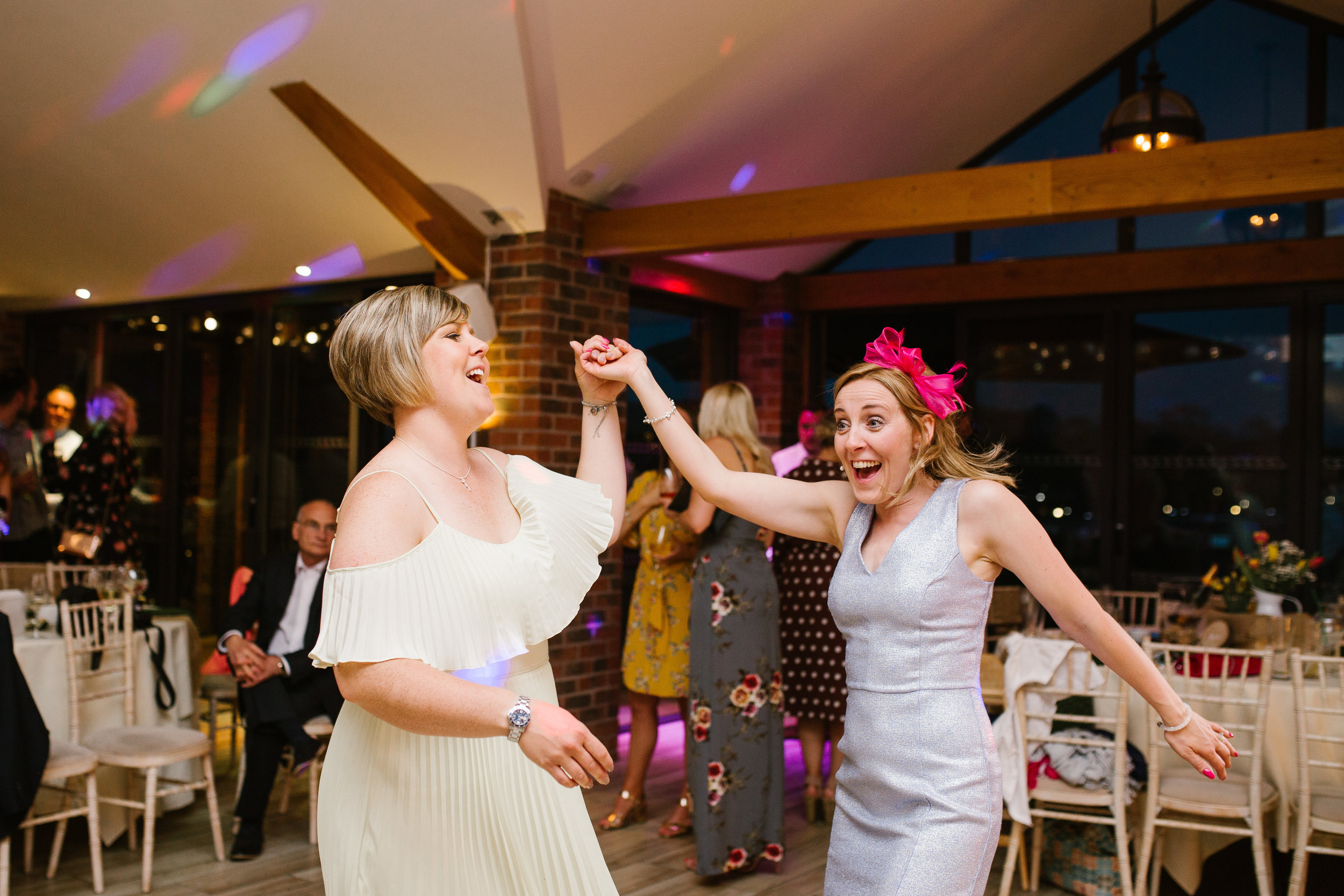 wedding guests having fun on the dance floor at the boat house at an awesome summer wedding