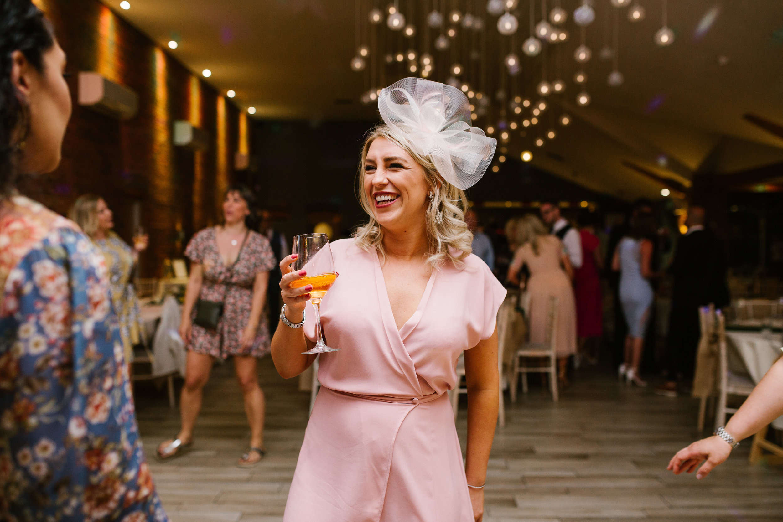 wedding guest dressed in pink holding wine standing on the dance floor smiling