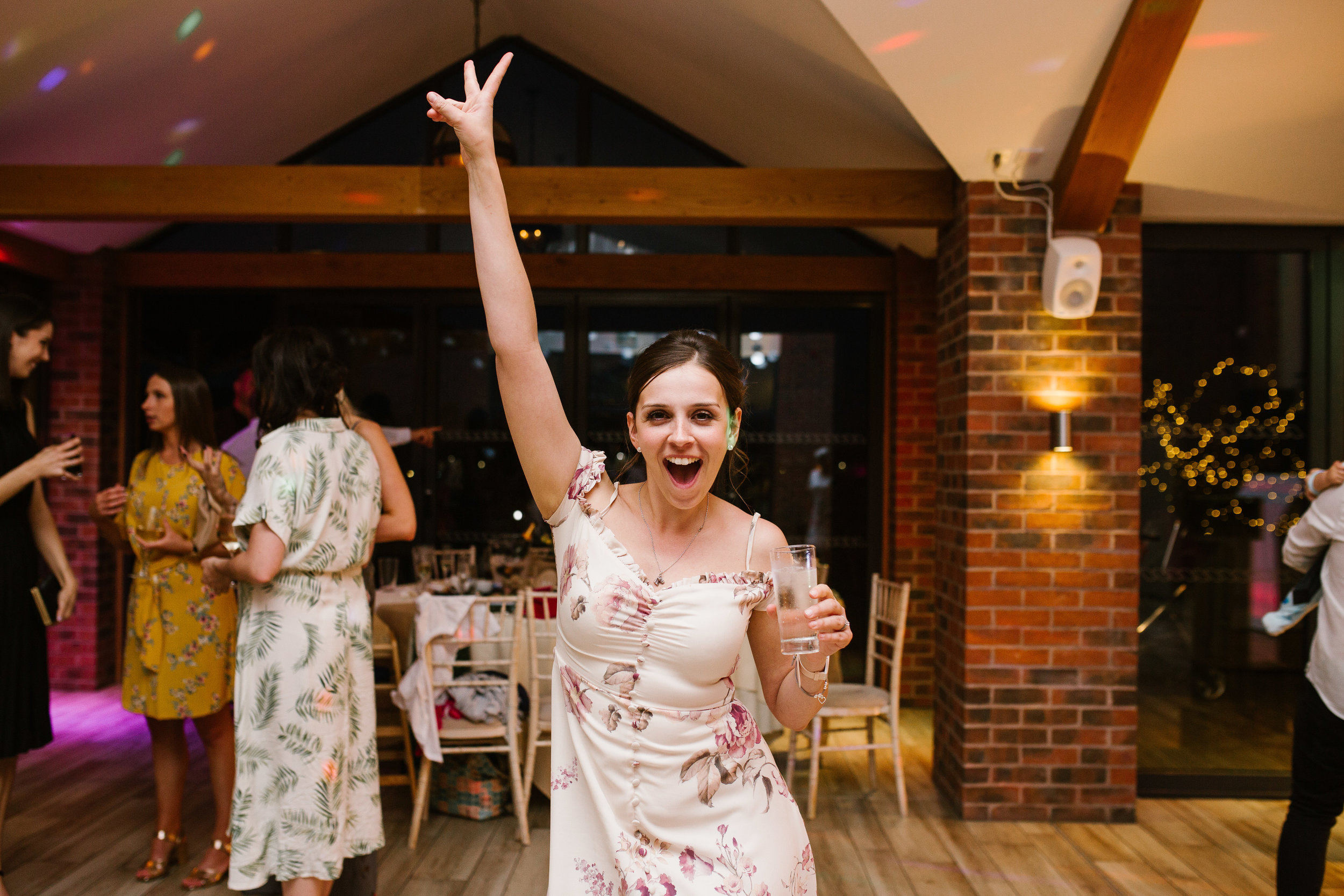 wedding guests celebrating with her hands in the air cheering