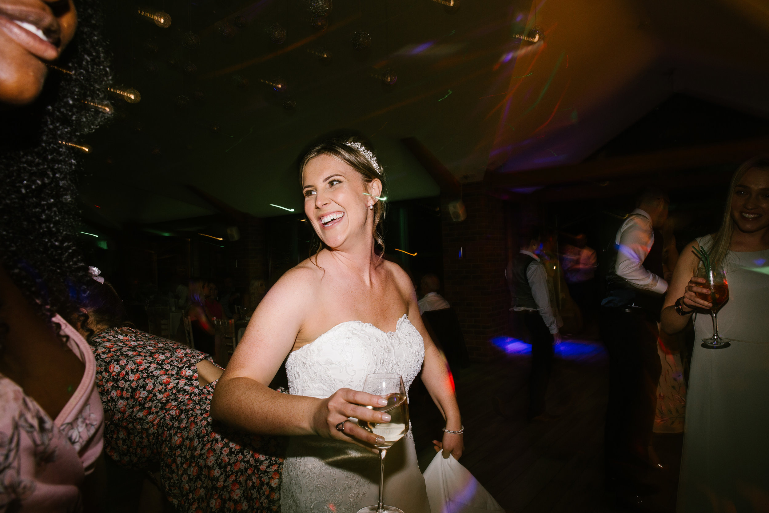 natural photo of the bride laughing on the dancefloor