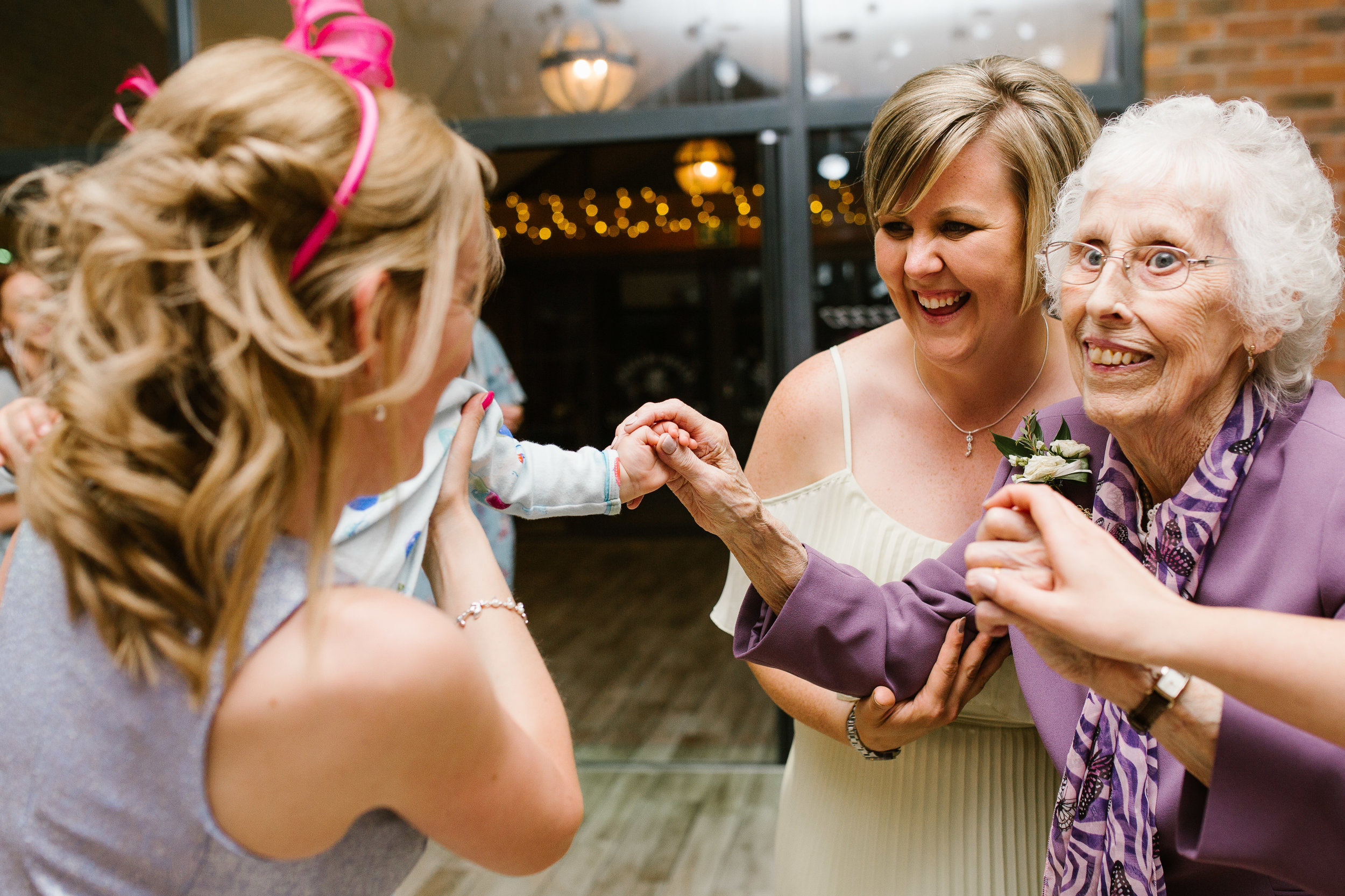 great nan and toddler hold hands together on the dance floor at wedding party at aston marina boat house wedding venue in staffordshire